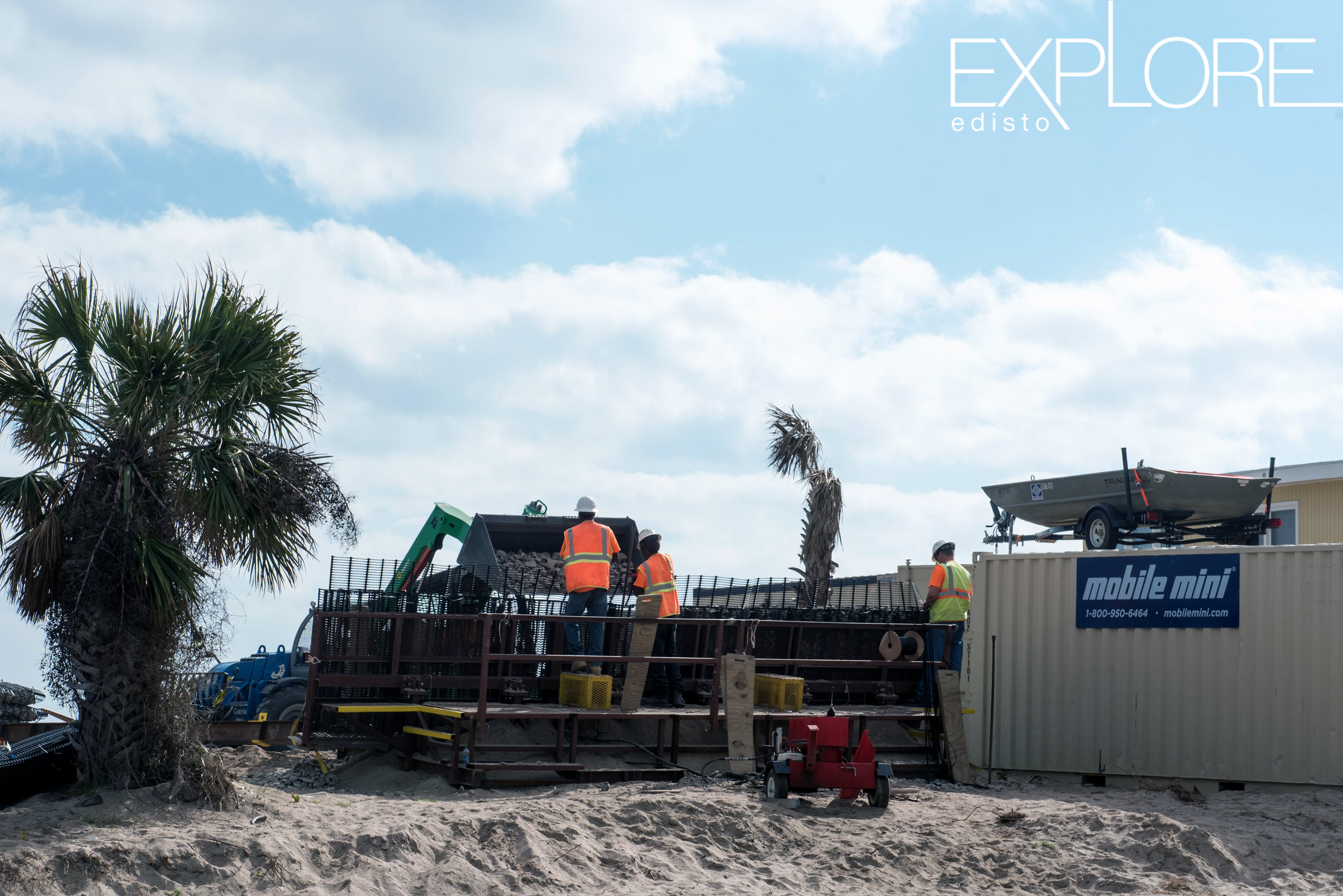 Men at work next to container on the beach during beach nourishment.