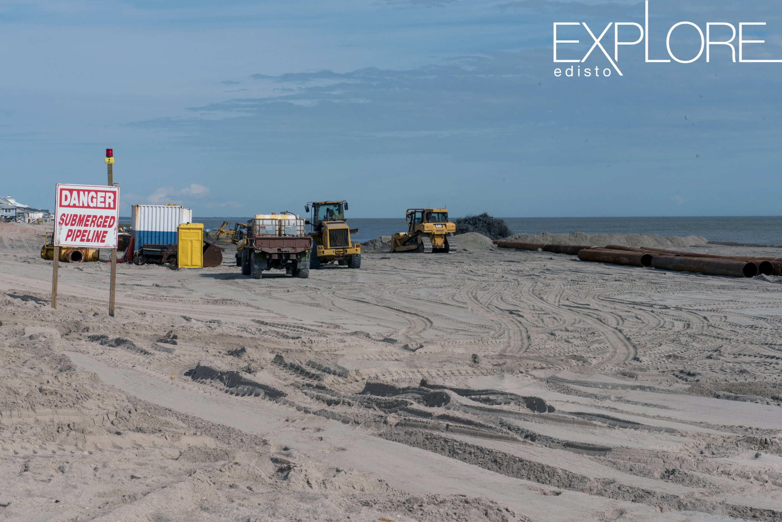 Danger, Submerged Pipeline sign in front of tractors at work on beach renourishment.