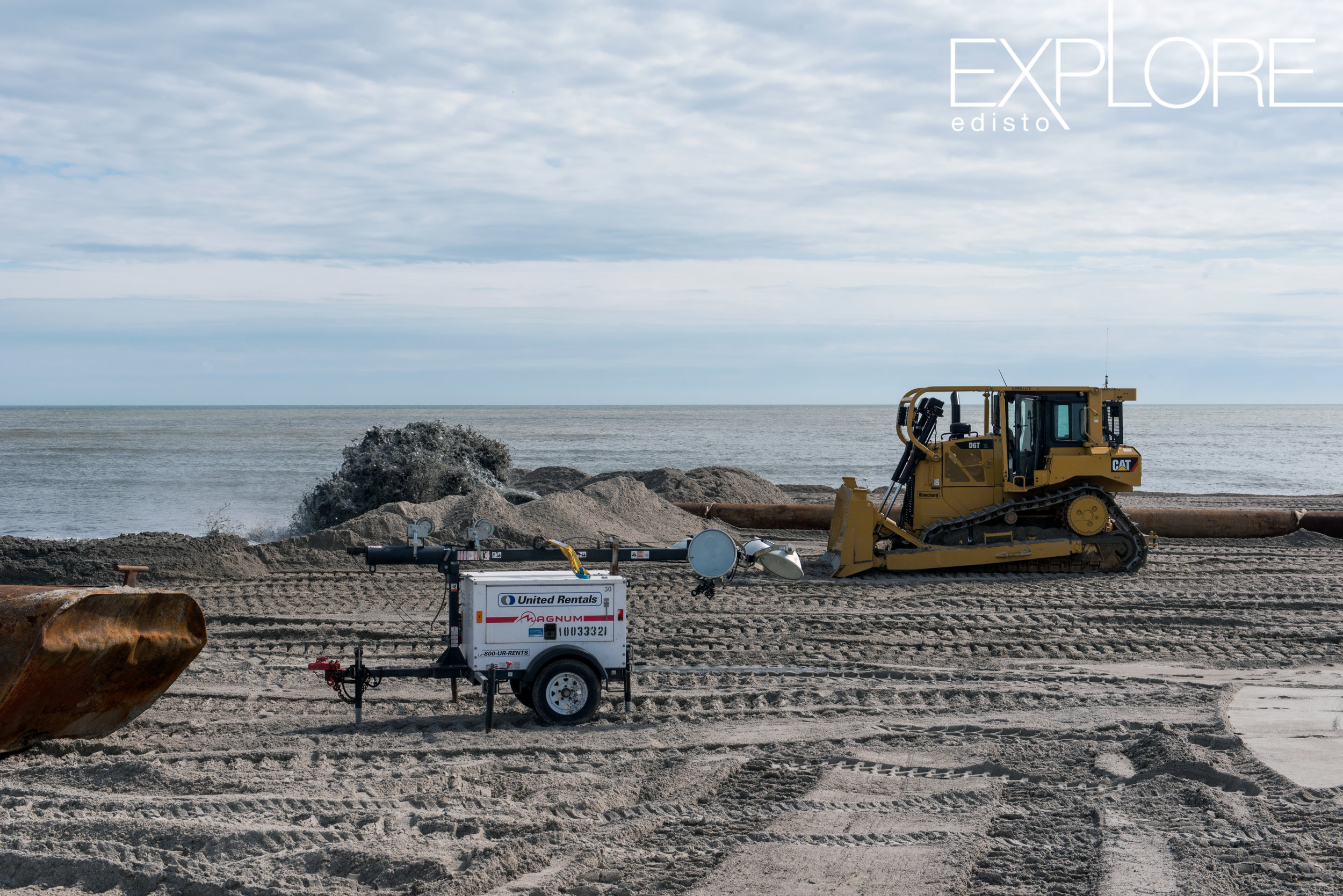 Tractor and sand being pumped onto the beach from the ocean.