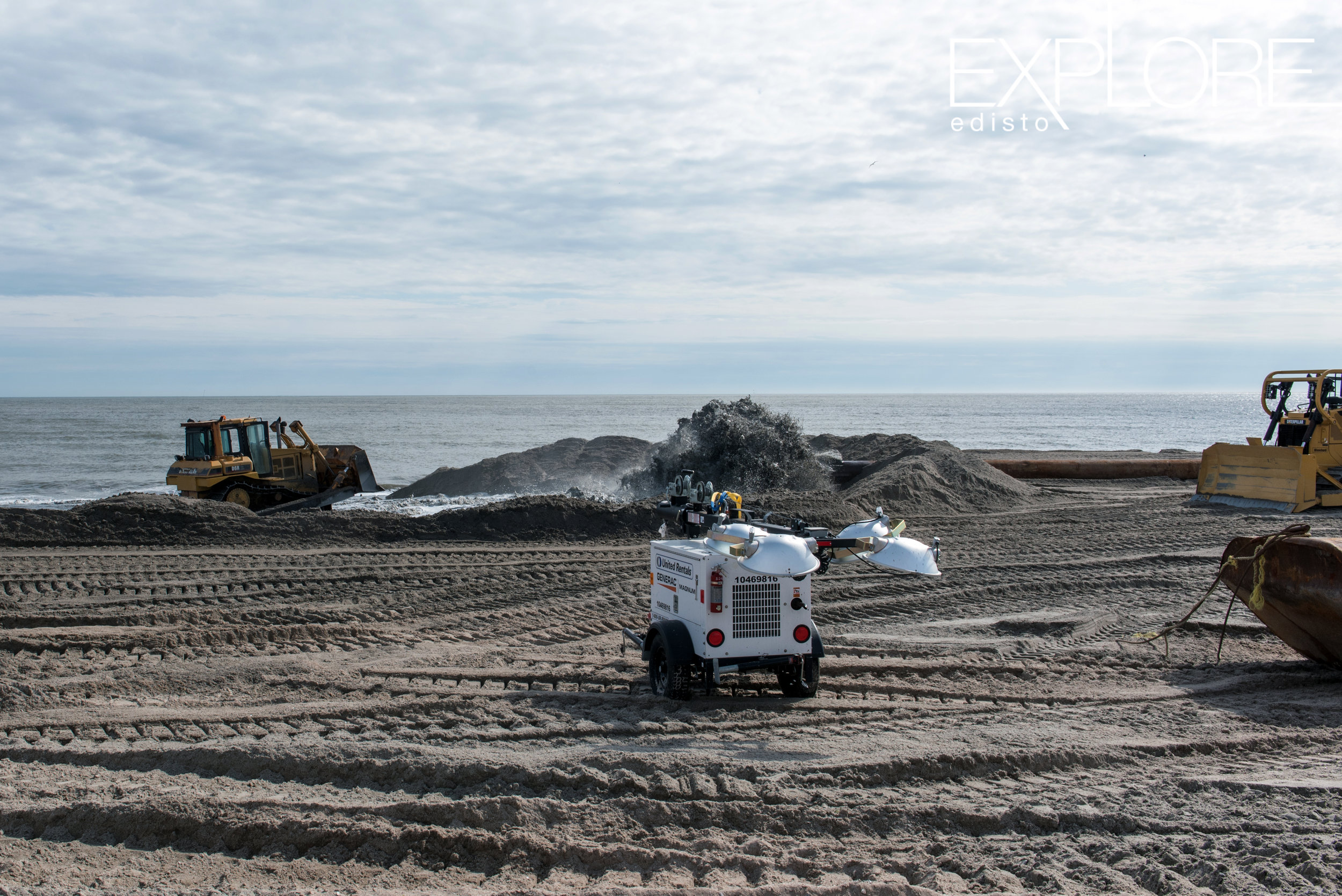 Tractors working and sand being pumped onto the beach from pipeline in ocean.
