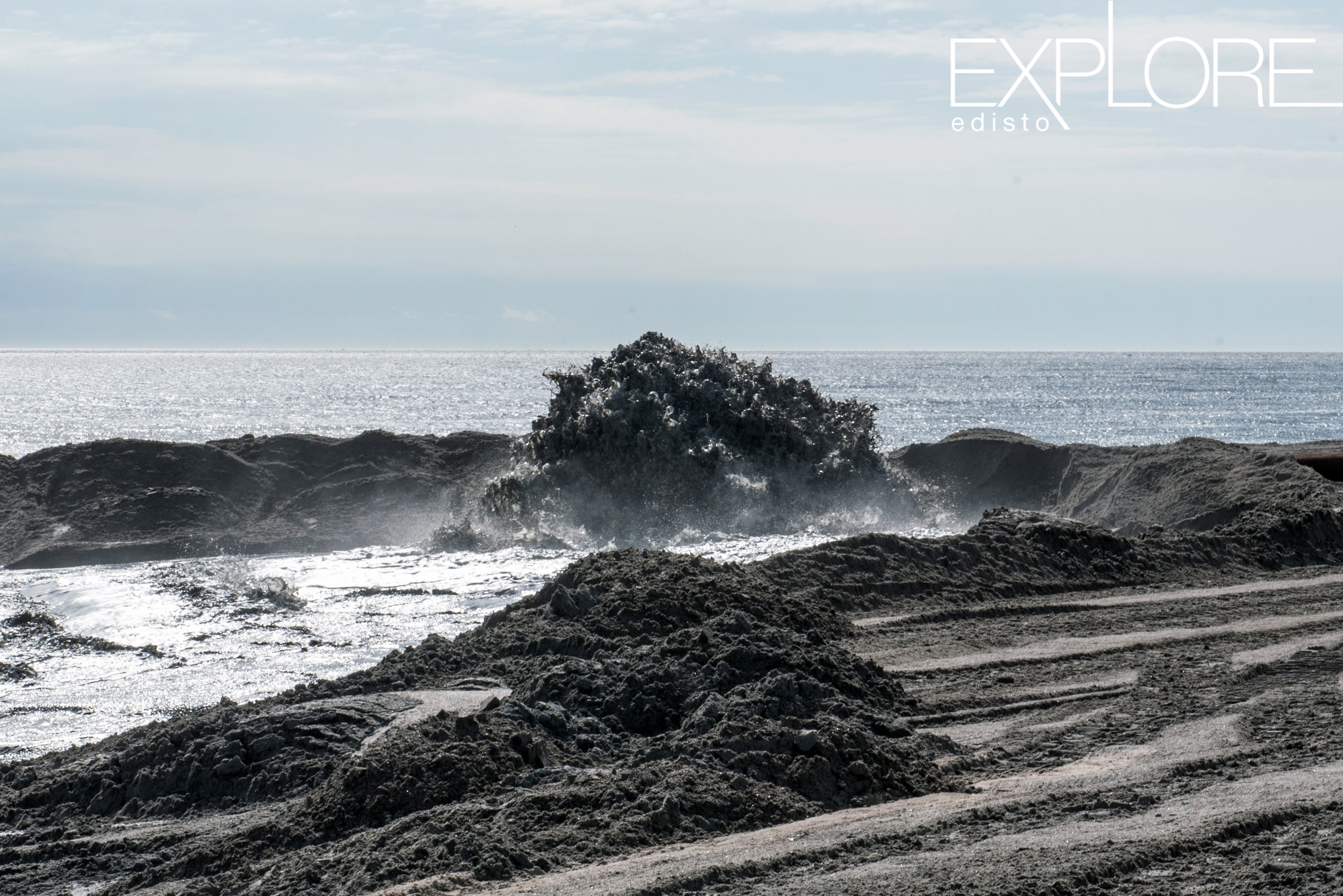 An explosion of sand as it is blasted onto the beach during beach nourishment at Edisto Beach, SC.