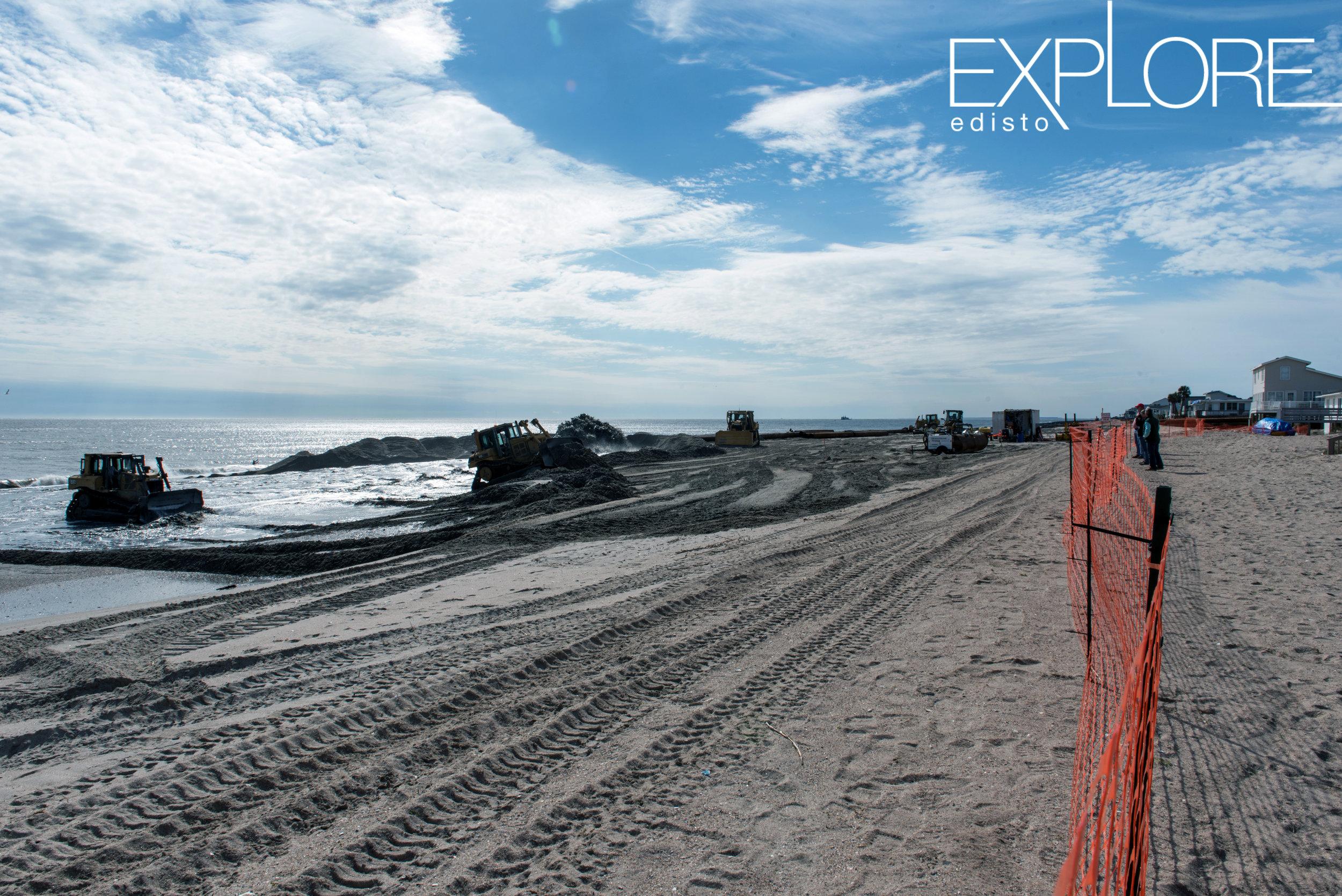 Orange fencing marks a work area during beach renourishment.