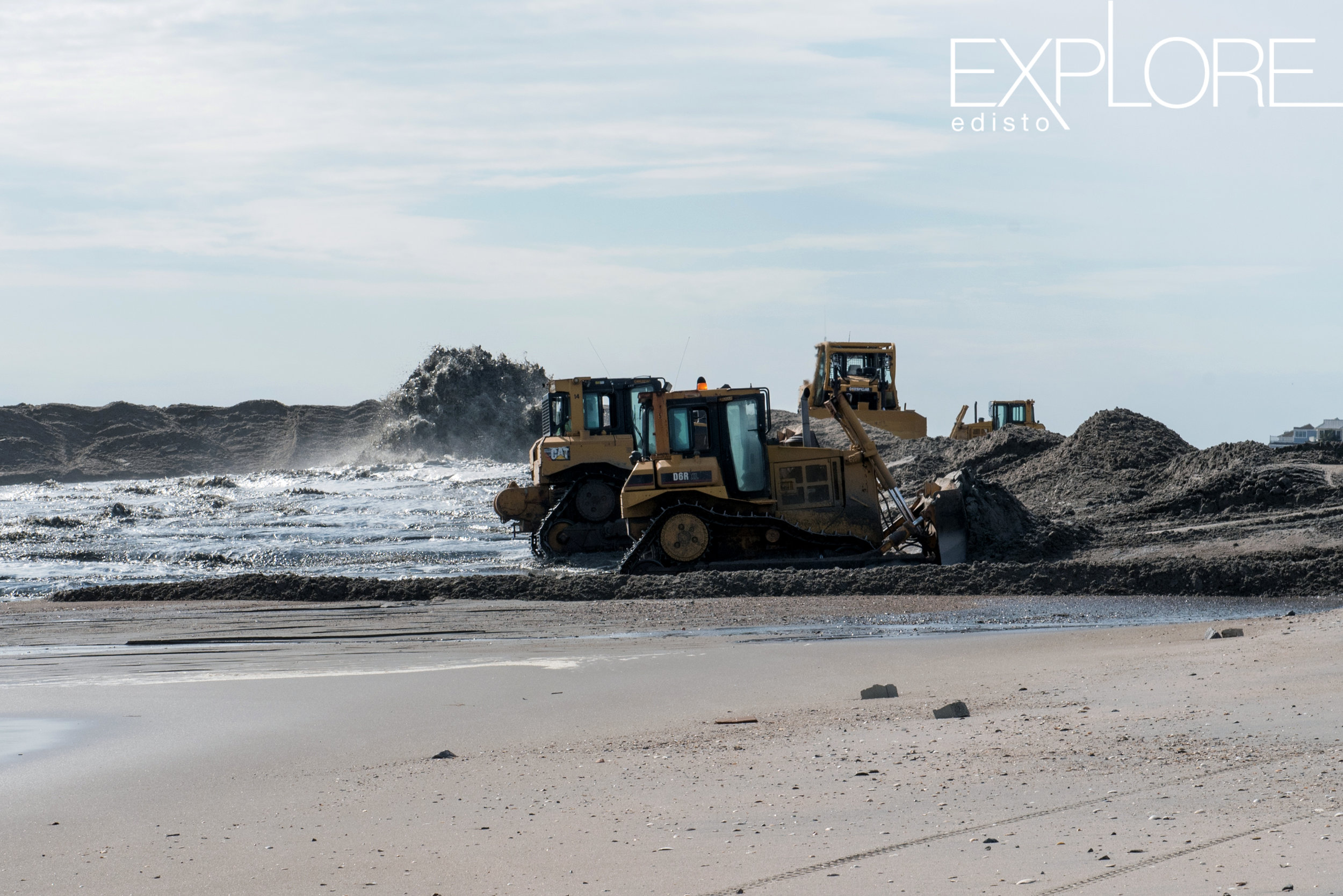 Tractors pushing sand onto the beach while it is being blasted to the shore from a pipe in the distance.