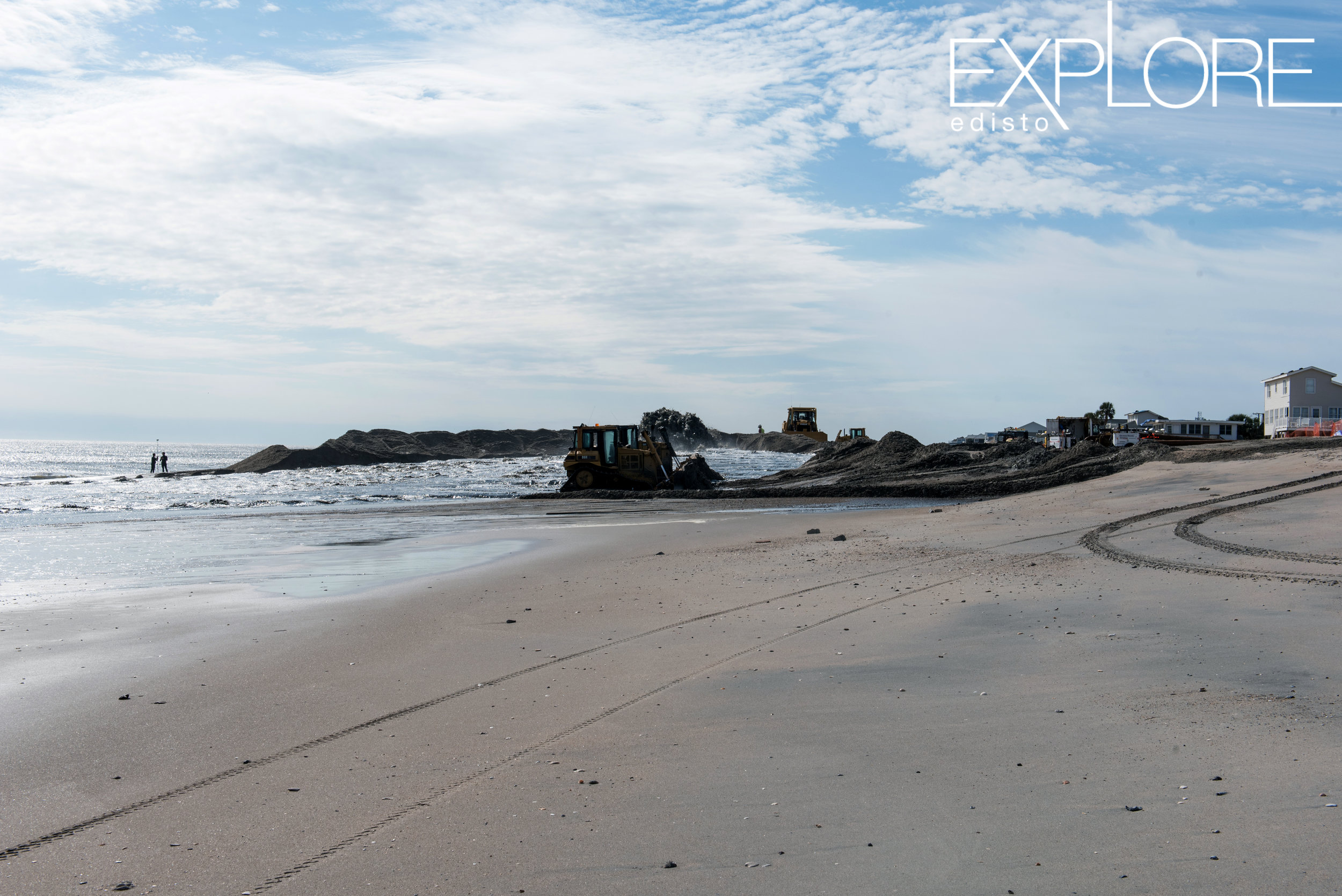 Tractors on the beach from a distance during beach nourishment.