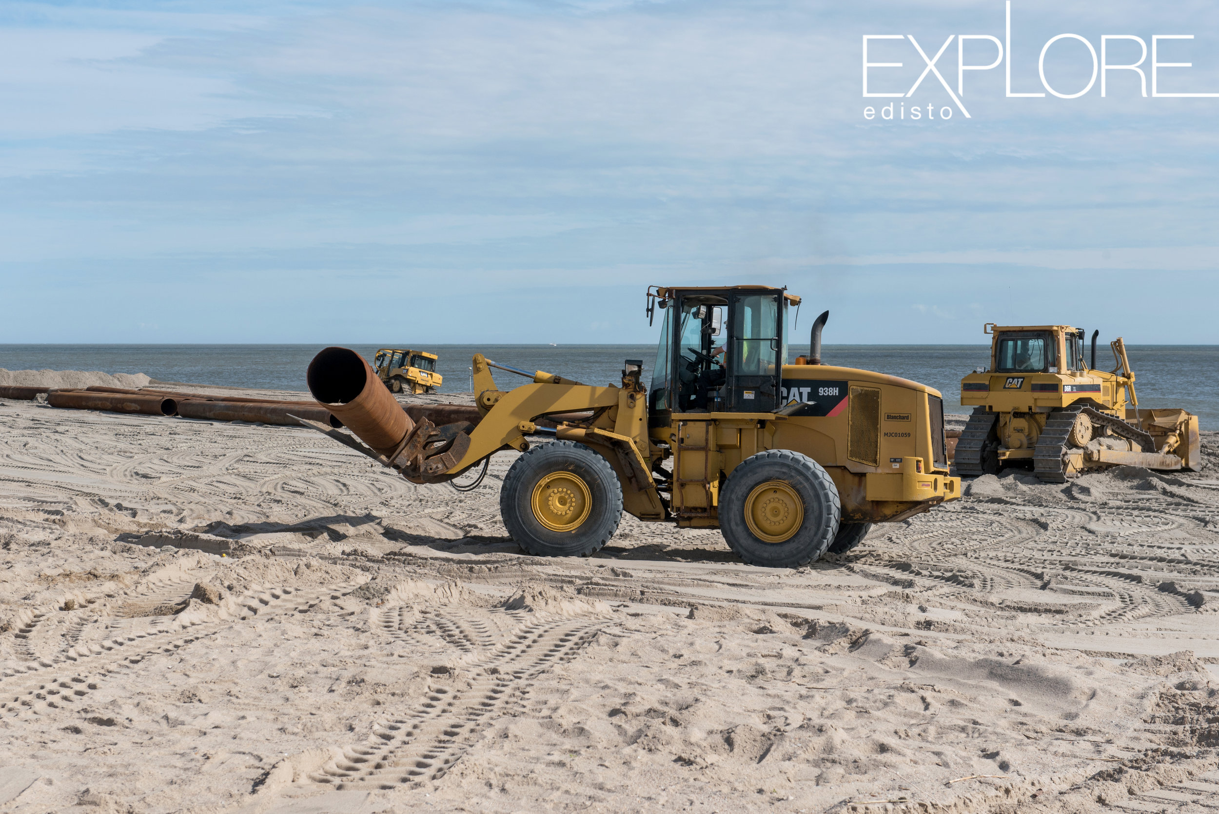 Tractor moves pipe on the beach during beach nourishment.