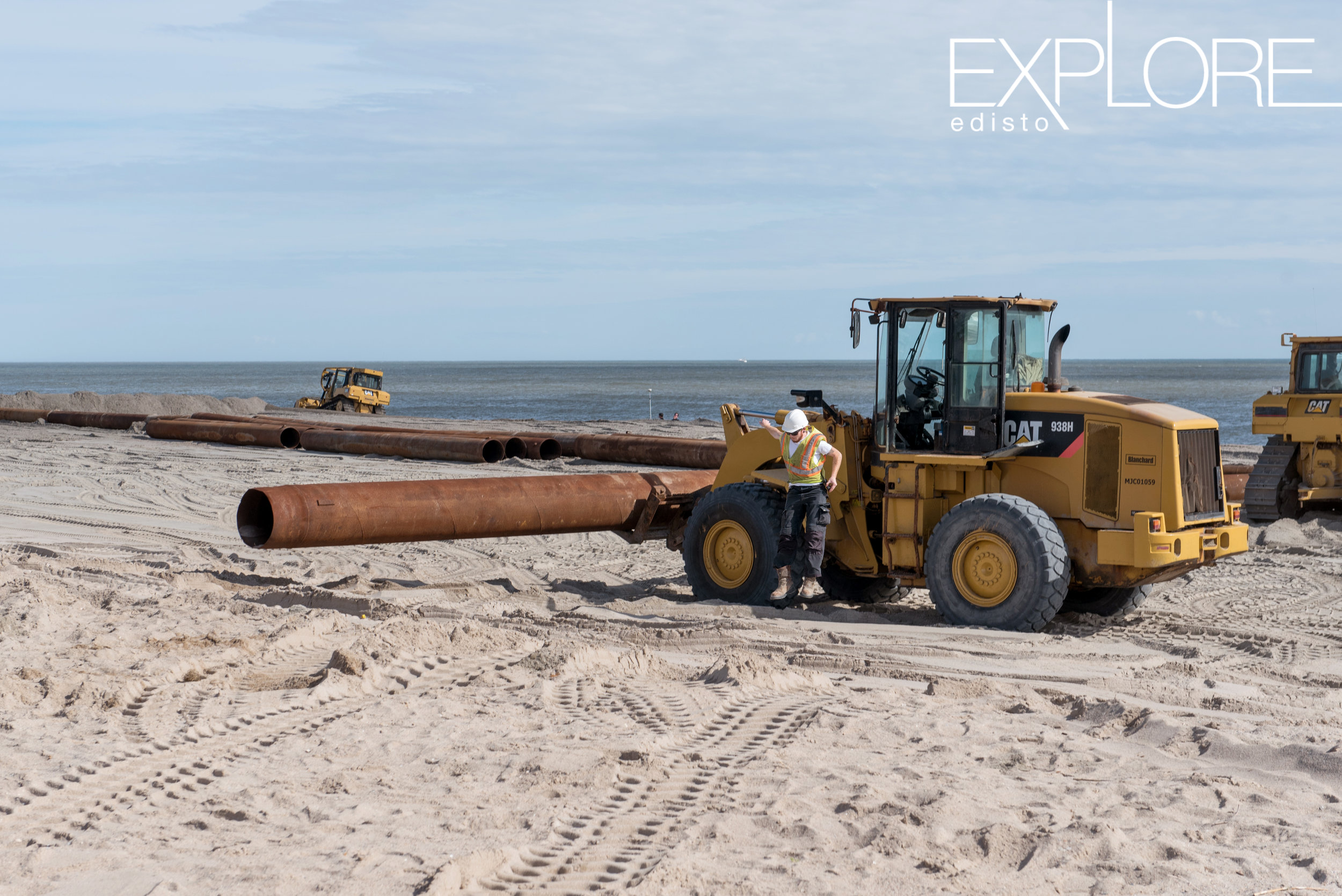 Man in hard hat jumps from tractor while working on the beach during beach renourishment.