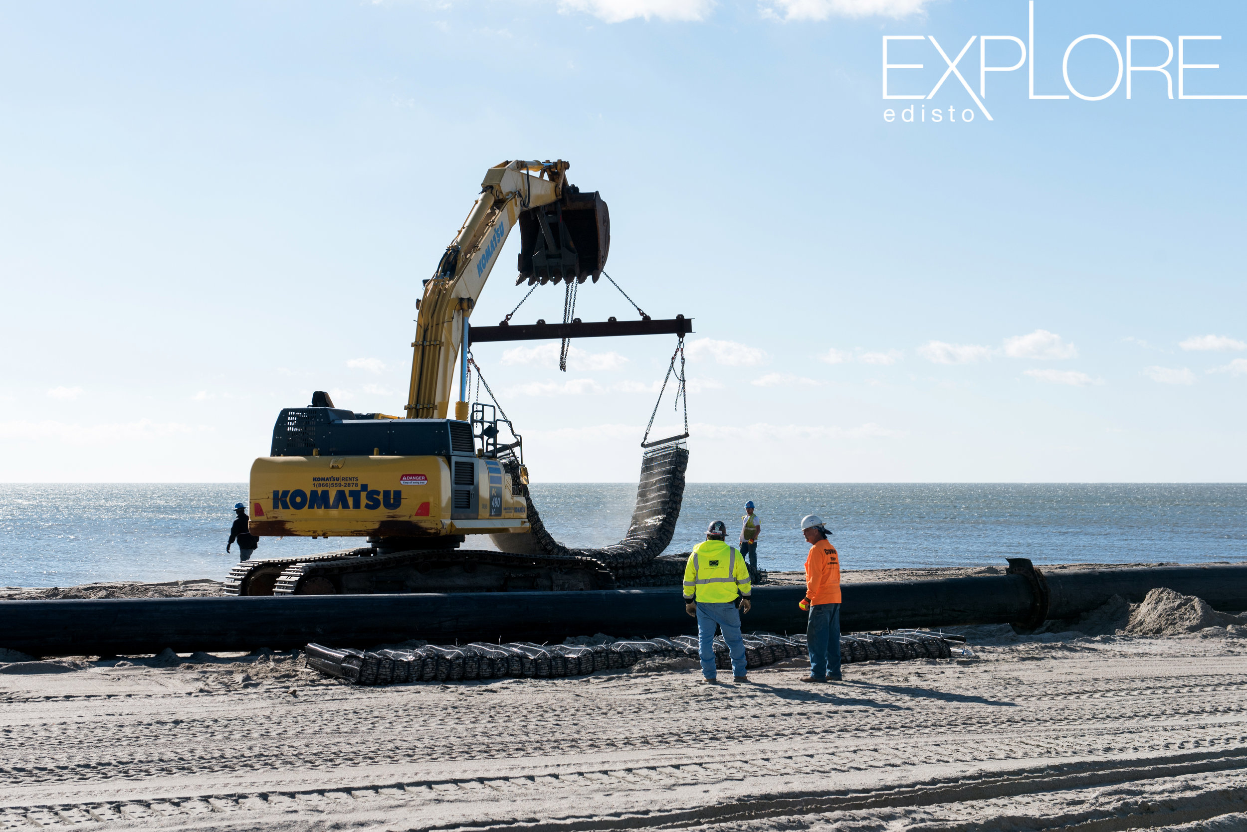 Crane moving rocks on the beach. Workers in foreground wearing neon orange and yellow.