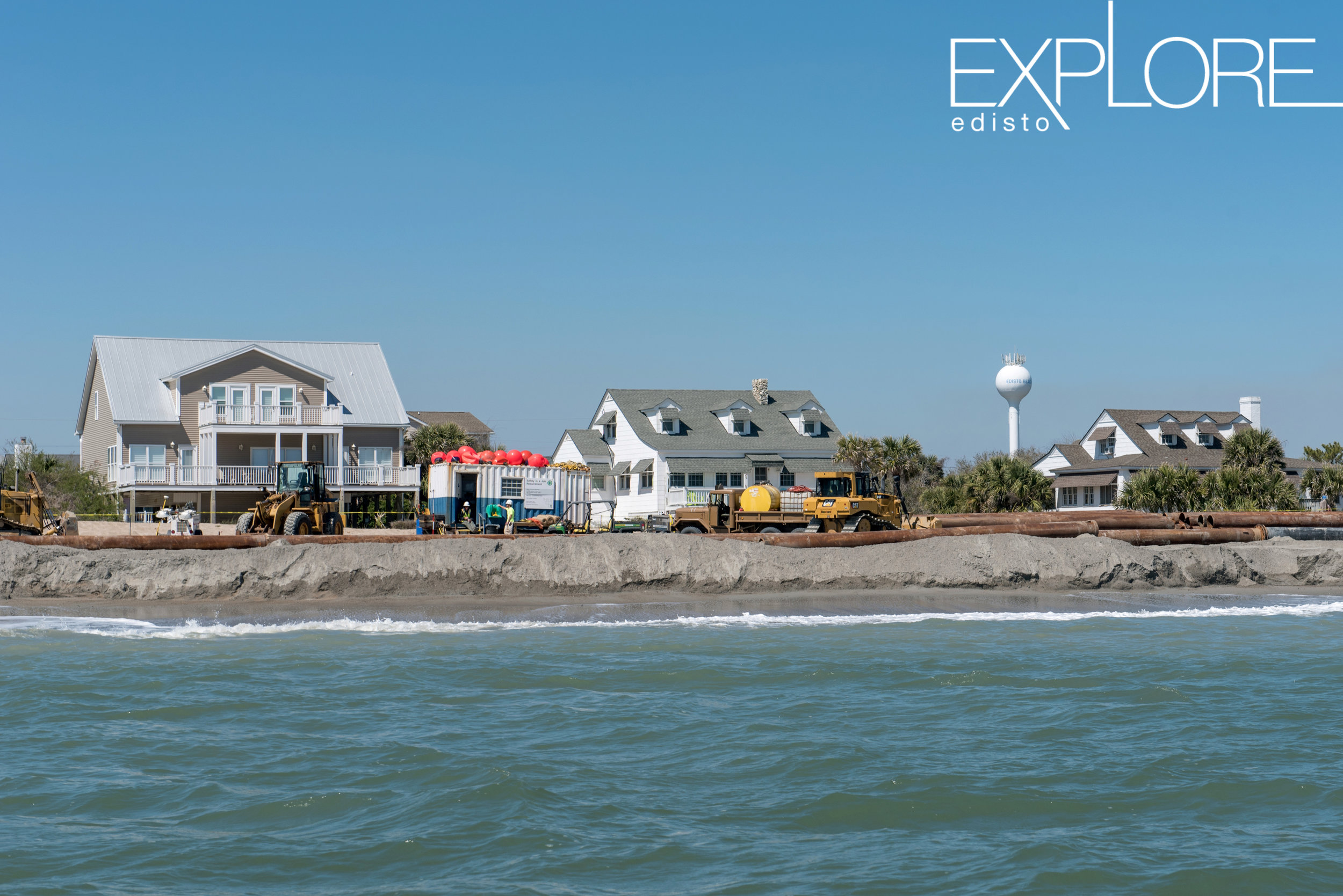 View from the ocean of tractors and crew working on the beach during beach nourishment. Houses and water tower in background.