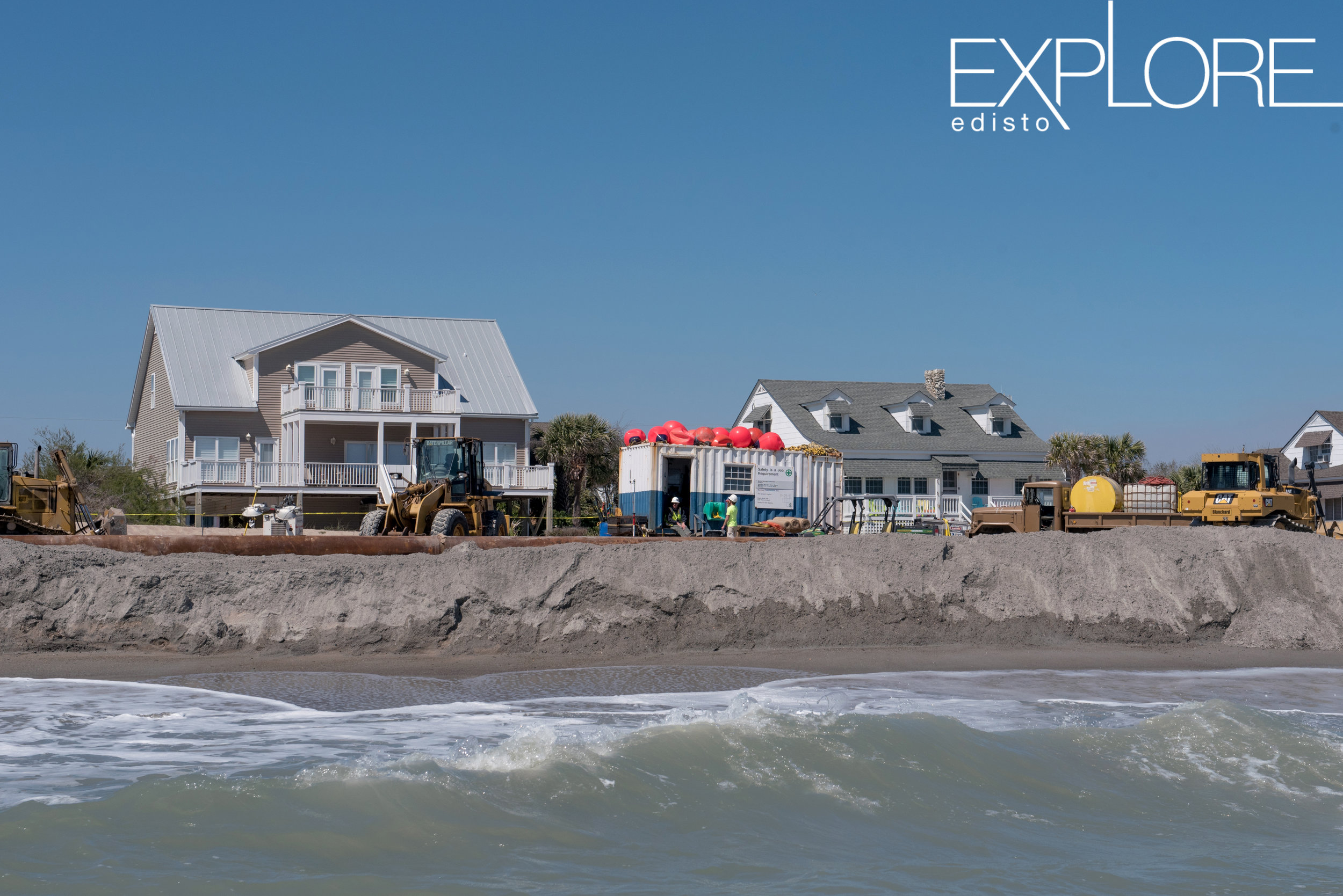 View of beach renourishment from the ocean. Container and tractors on beach with houses in background.
