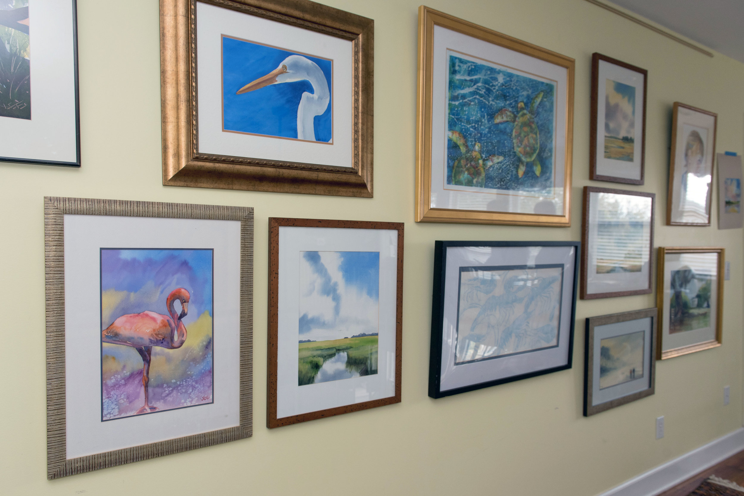 A collection of Bonnie Lee's artwork hanging on a wall.