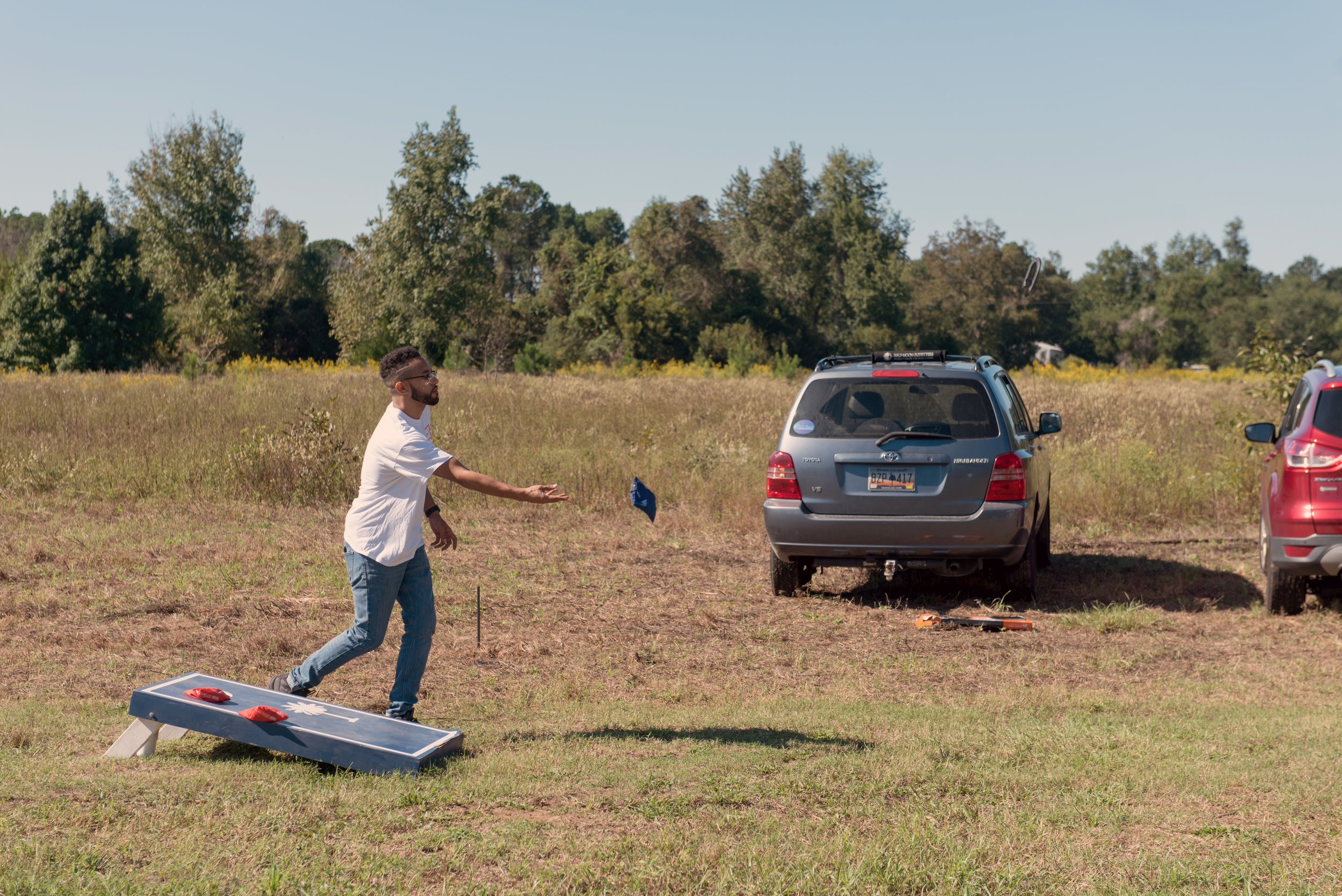 Young man tosses a blue bean bag while playing the game cornhole.
