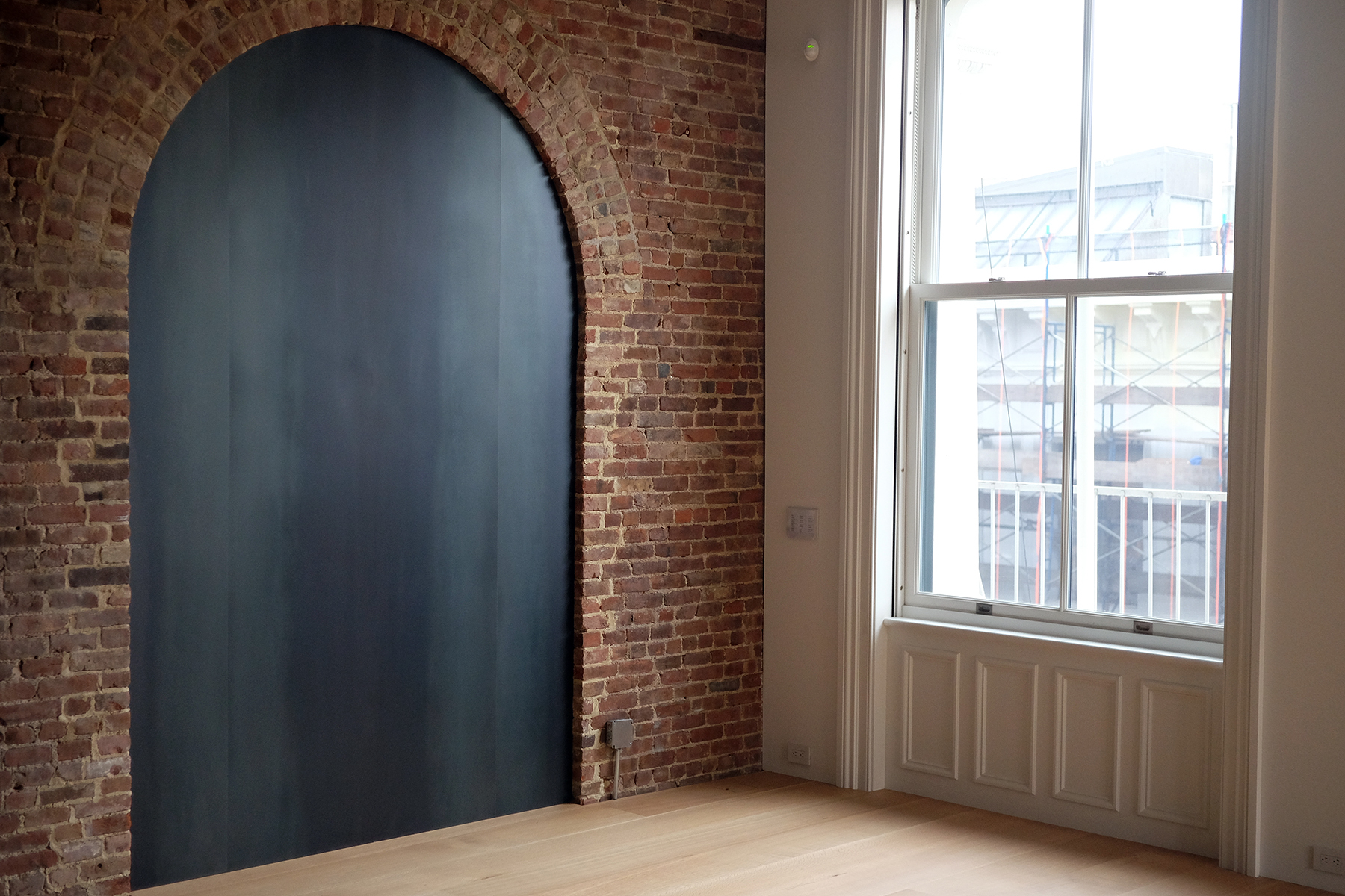 In this converted brush factory loft clear lacquered steel fills the archway in a brick wall...