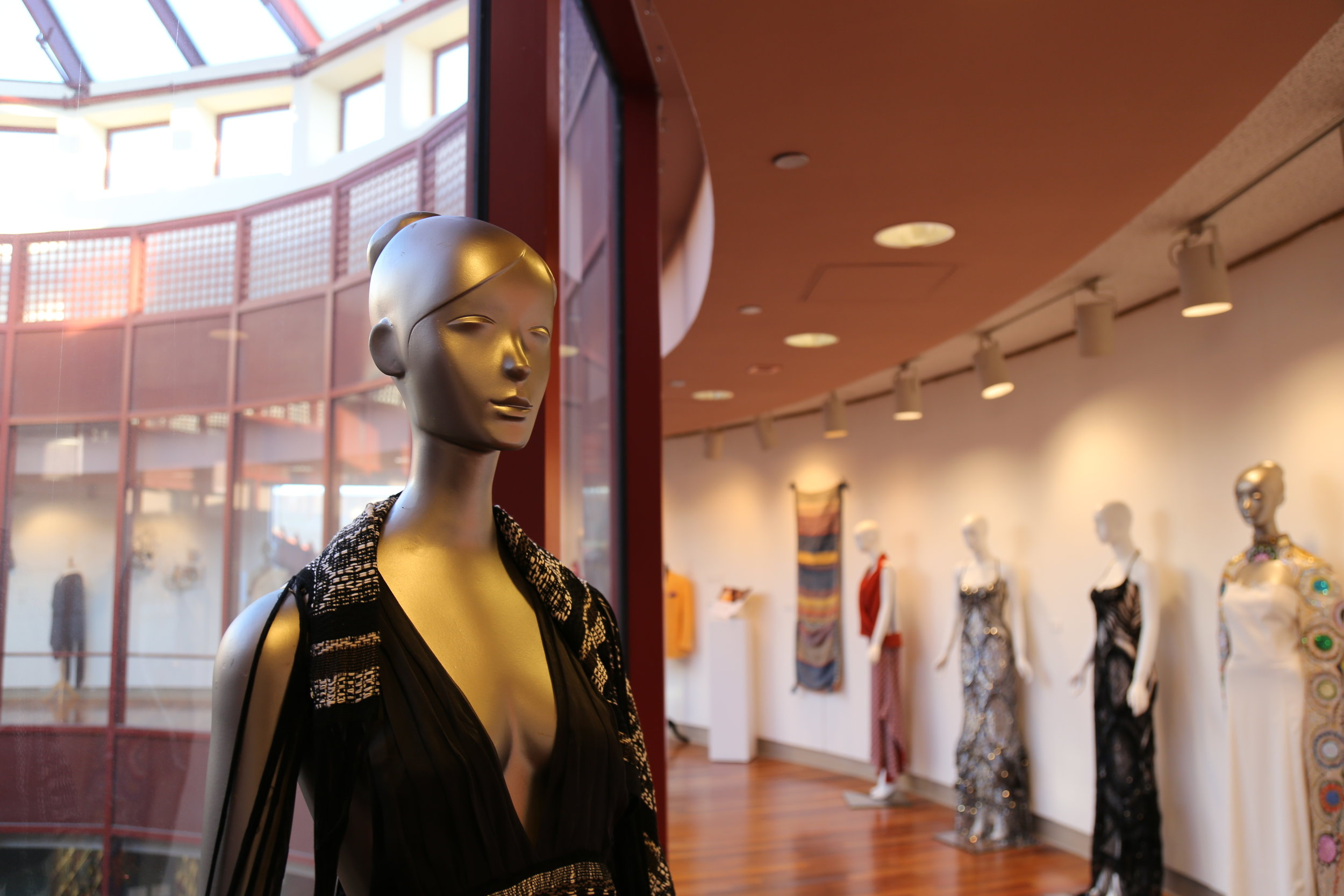 Foreground: An organic silk wedding dress by CANGARI takes on new life after being dyed black; the train of the gown becomes a shawl. Background: Garments on display by Pucci and FrancyG. Photo courtesy of Queens College Art Center.
