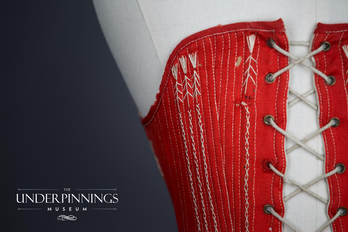 Red midbust corset with flossing, c. 1860s, The Underpinnings Museum. Photography by Tigz Rice.