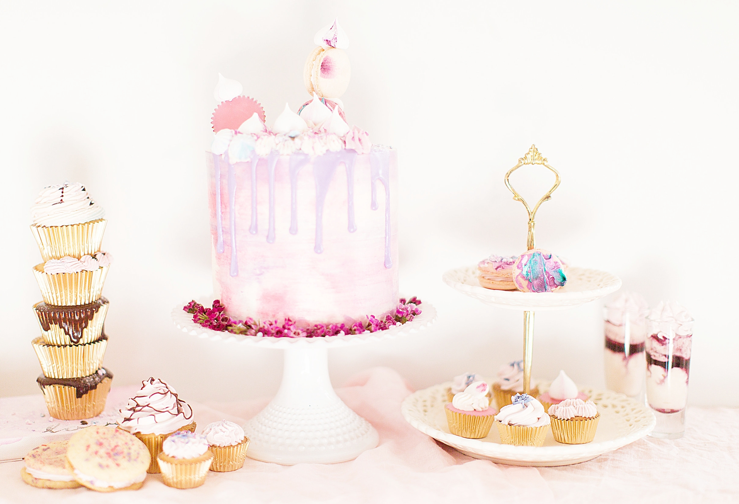 Here's a shot of most of the products that were included that day. A tall drip cake, cupcakes, mini cupcakes, macarons, cookie sandwiches, and dessert shooters. Perfect photography by  Emily Katharine Photography .