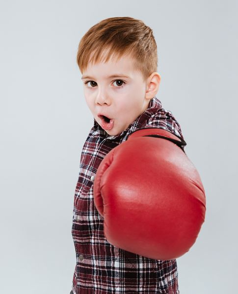 Litle boy in boxing gloves standing and fighting
