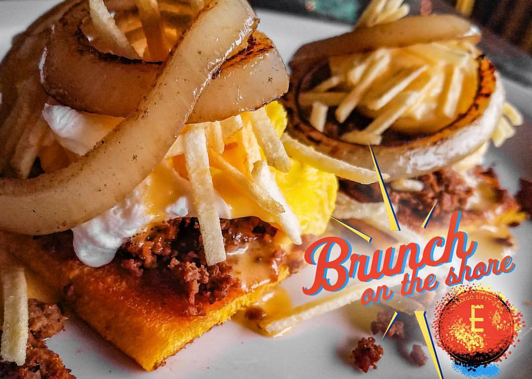 Our Brittany Benedict will knock you off your feet! Fresh Medianoche (Sweet) Bread, Cuban style ground beef, Poached Egg, Creamy Tomato Hollandaise Sauce, Crispy Potato Sticks, topped with Caramelized Onions