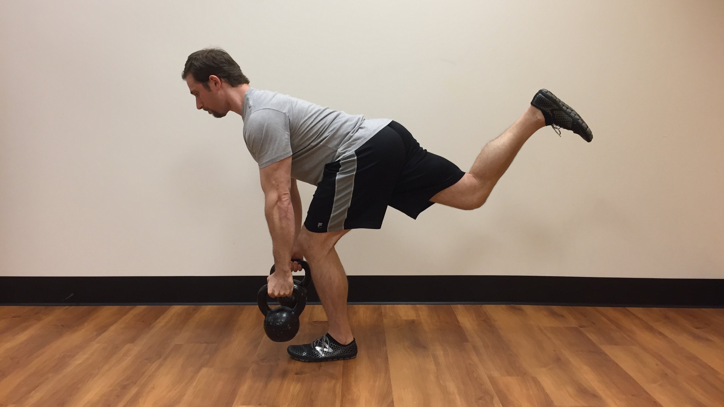 Proper Single Leg RDL with soft knee in support leg and 90 degree bend in elevated leg