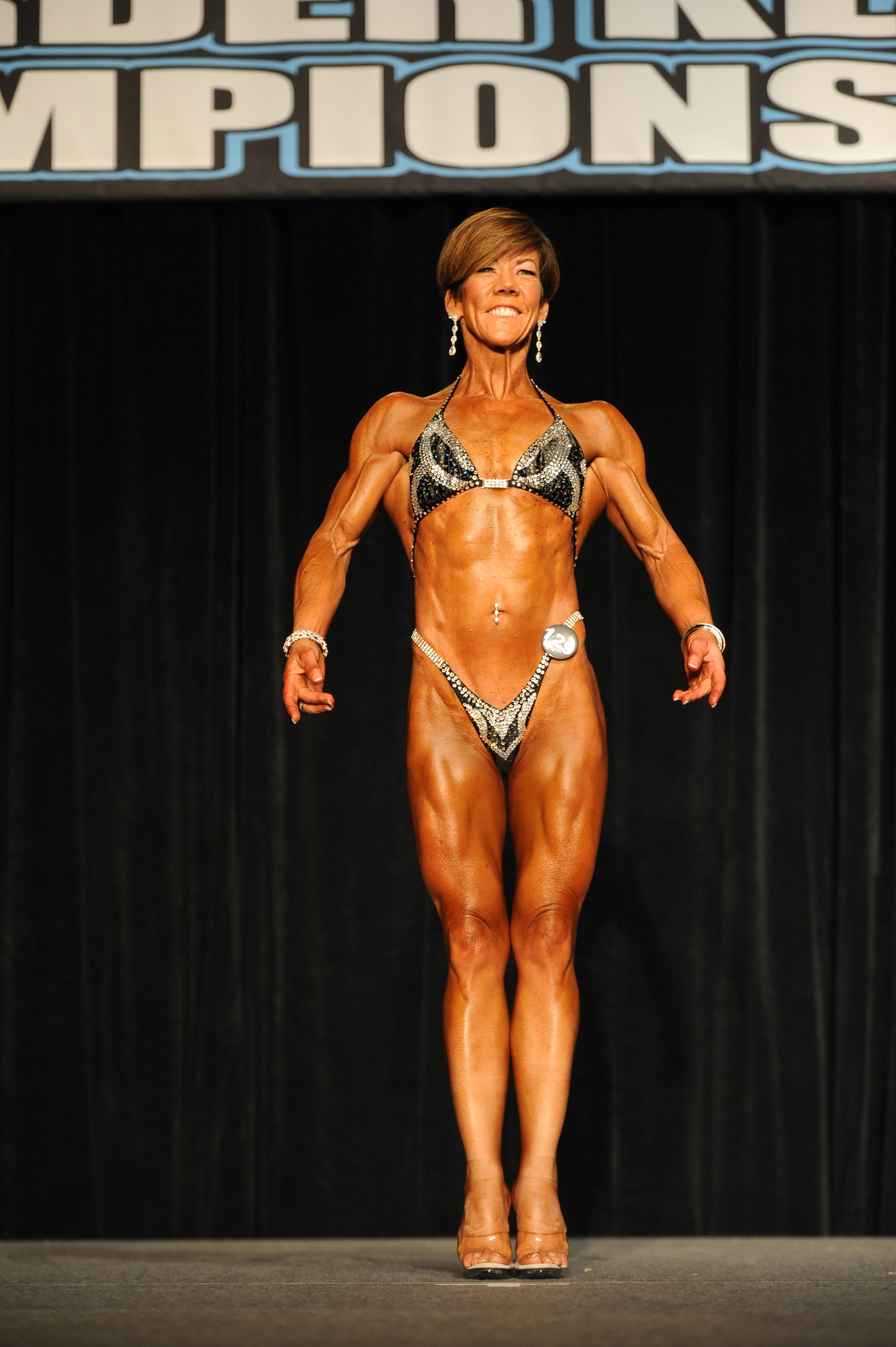 Leslie Petch Lee demonstrating her front pose and winning her latest NPC figure show
