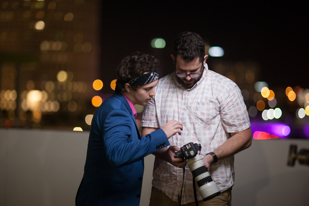 Deuce and Coleton reviewing images from their shoot in front of the Tampa Skyline