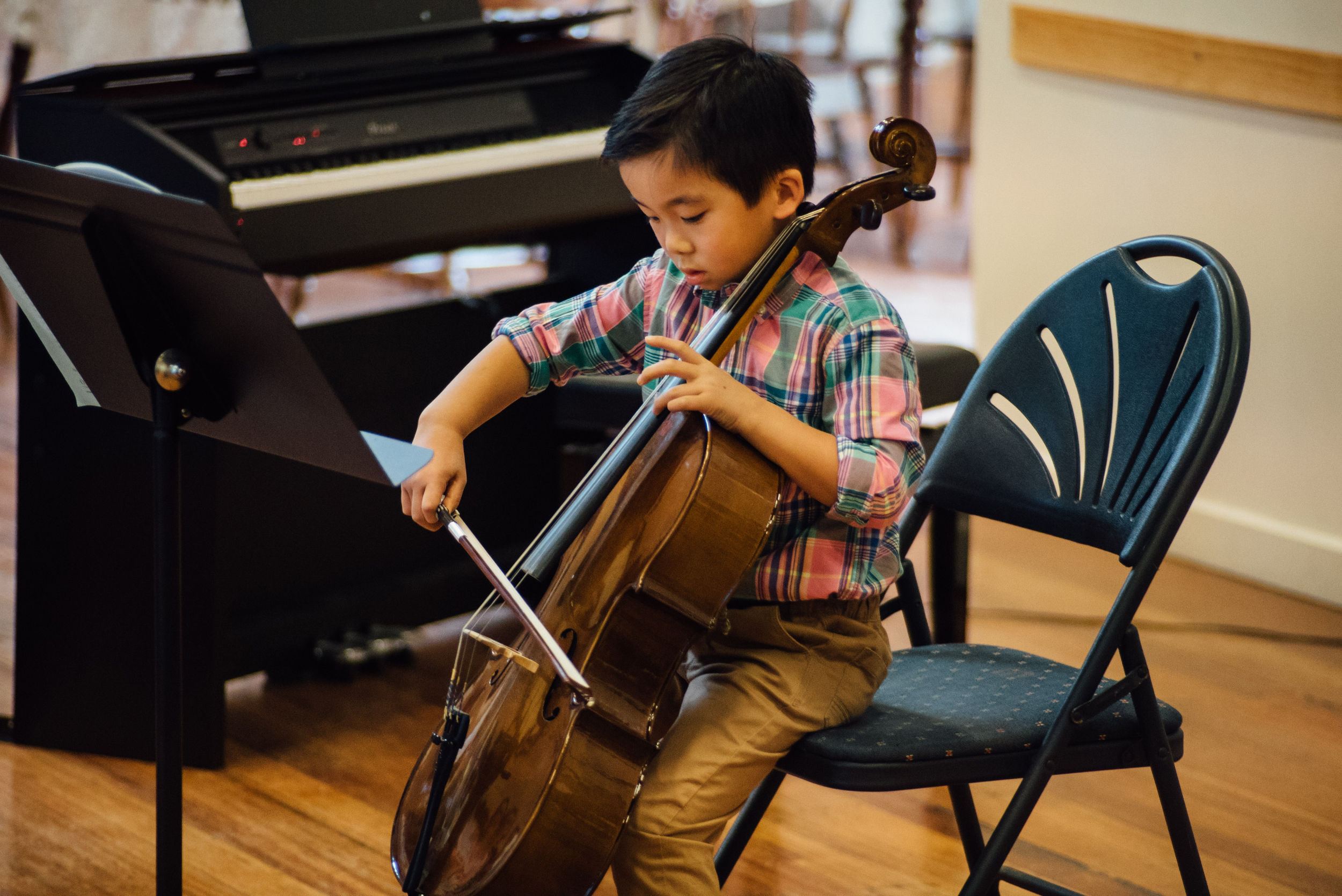 Boy performs cello at a school concert