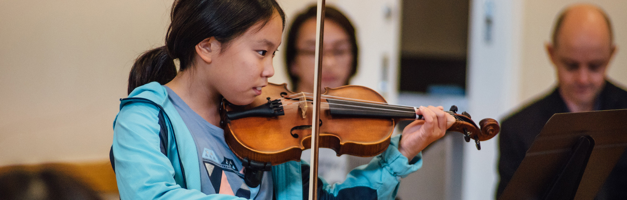 A girl playing violin at a whitehorse music school recital