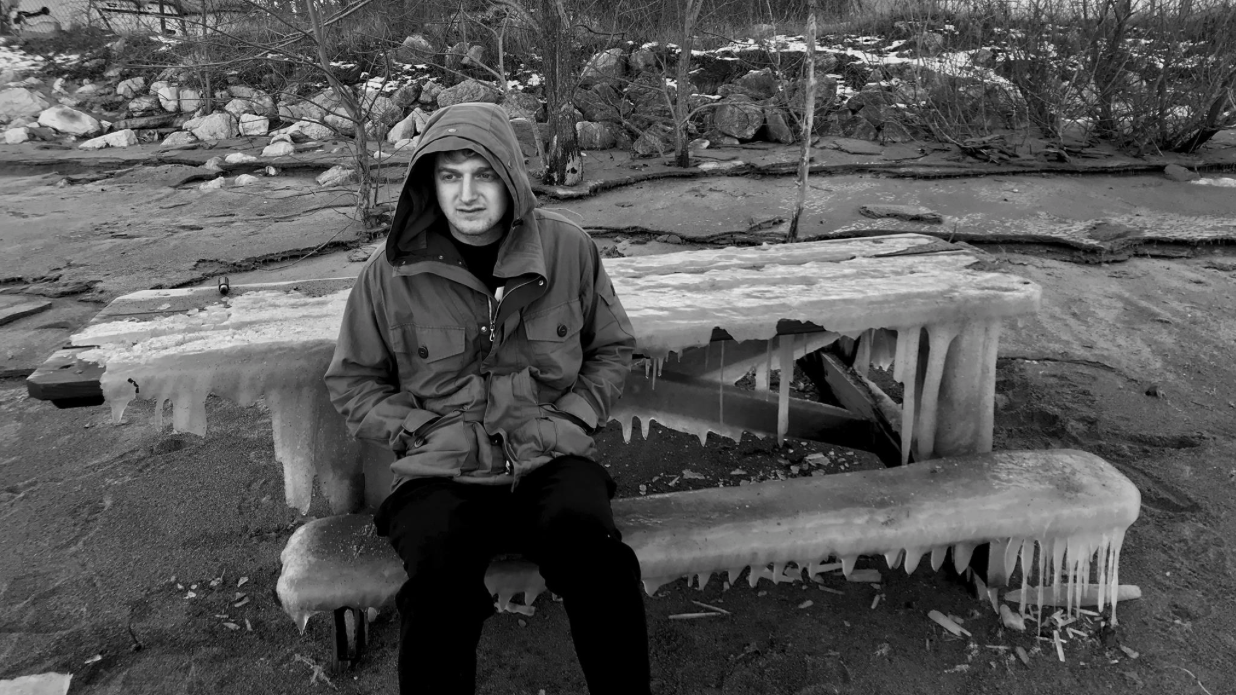 Man in jacket sitting on icy picnic bench