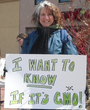 加州數家非盈利組織正聯手醞釀一項公投議案,推動「標注轉基因食品(GMO label)」立法。圖中婦女舉著「我想知道這是不是轉基因產品」的牌子。(圖片來源:Flickr Creative Commons)。