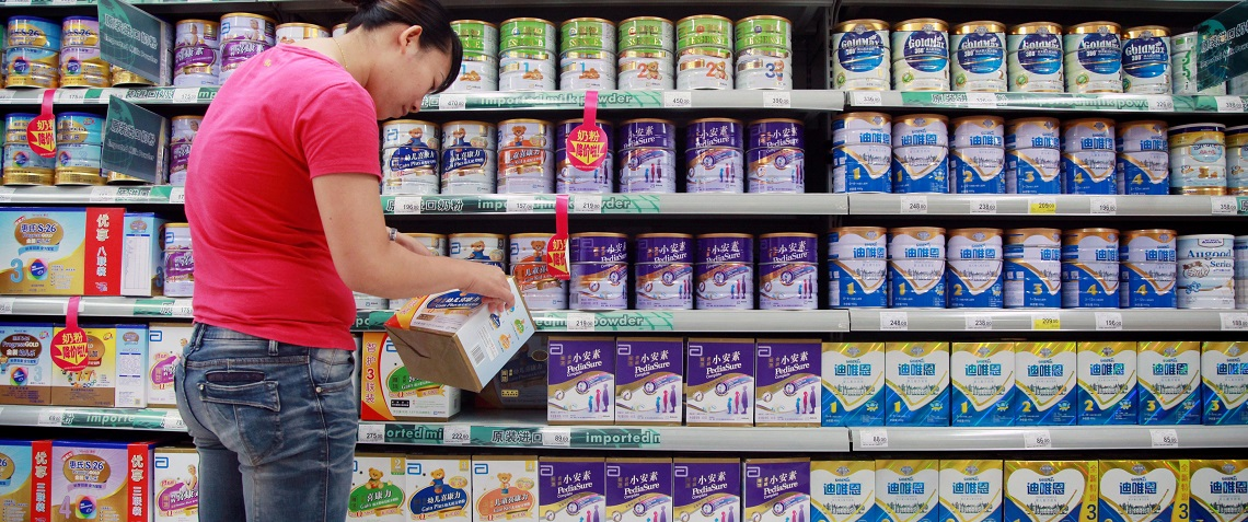 A customer selects baby milk in a supermarket in Haikou, south China's Hainan province. Photo: STR/ AFP/ Getty Images.