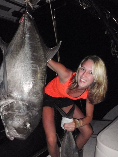 Girl with a huge fish she caught on a fishing charter holiday