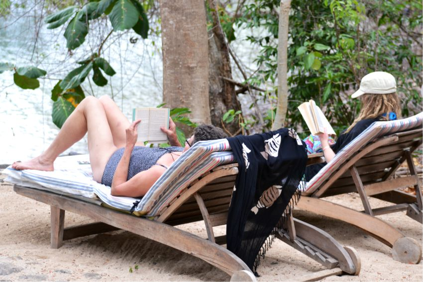 Two Ladies relaxing and reading in the sun on the beach at Saktia Lodge