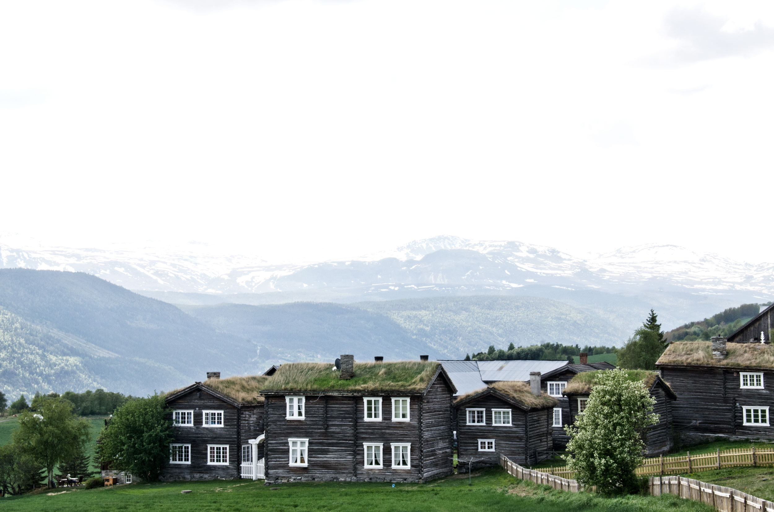 PÅ ØVSTE HYLLE: Den historiske garden Kvarberg Nedre ligg høgt og fritt i det unike kulturlandskapet Nordherad i Vågå. Jotunheimen ser du i horisonten - boligområdet Kvarbergåsen ligg i fjellfuruskogen bak fotografen sin ståstad.