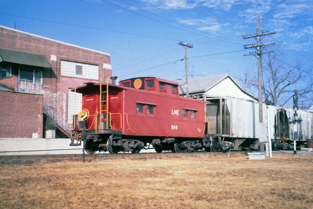 "No. 580 brings up the rear of a CNJ train on the former L&NE at Green Street in Nazareth, PA on January 31, 1969.  The CNJ kept the five former L&NE cabooses close to home and lettered them ""LNE,"" but repainted them without a logo and added the large circle on the cupola.  (Charles Houser photo, Rudy Garbely collection)"