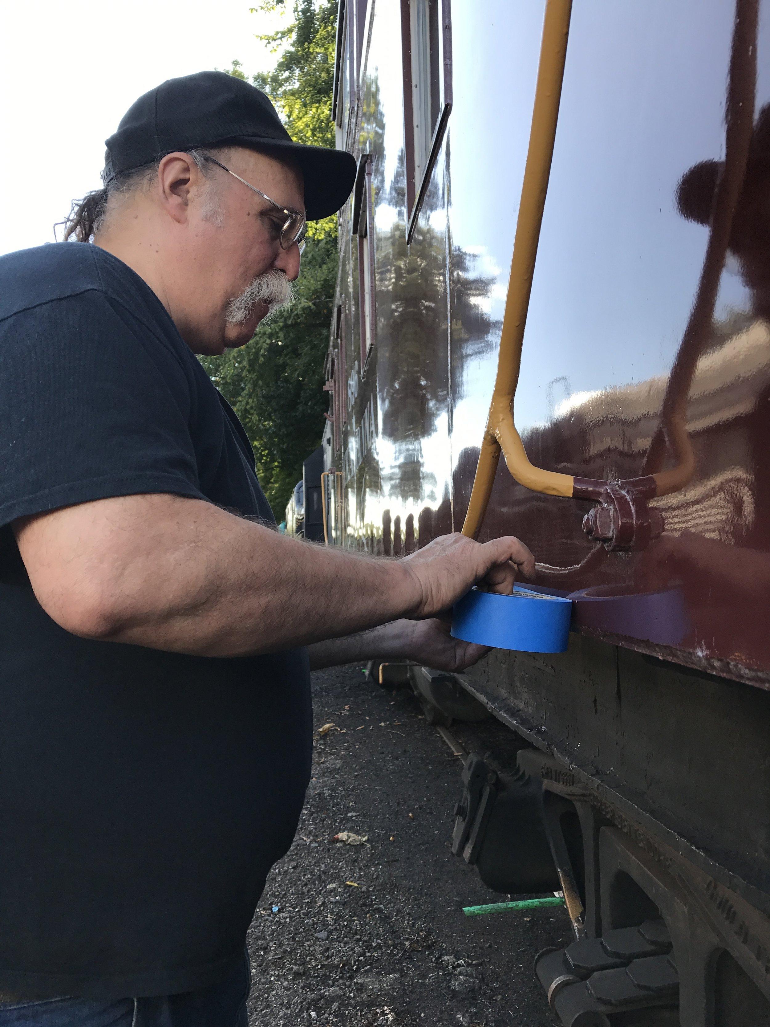Volunteer Jeff Jargosch masks off the car body to repaint the black underneath.