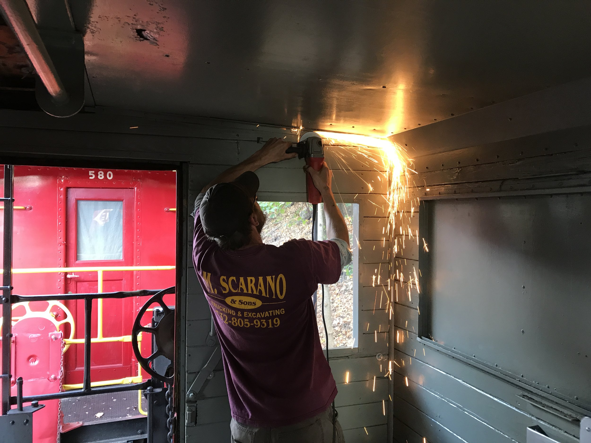 Erik Stenzel grinds off rusted screw heads to remove the rotten ceiling panels.