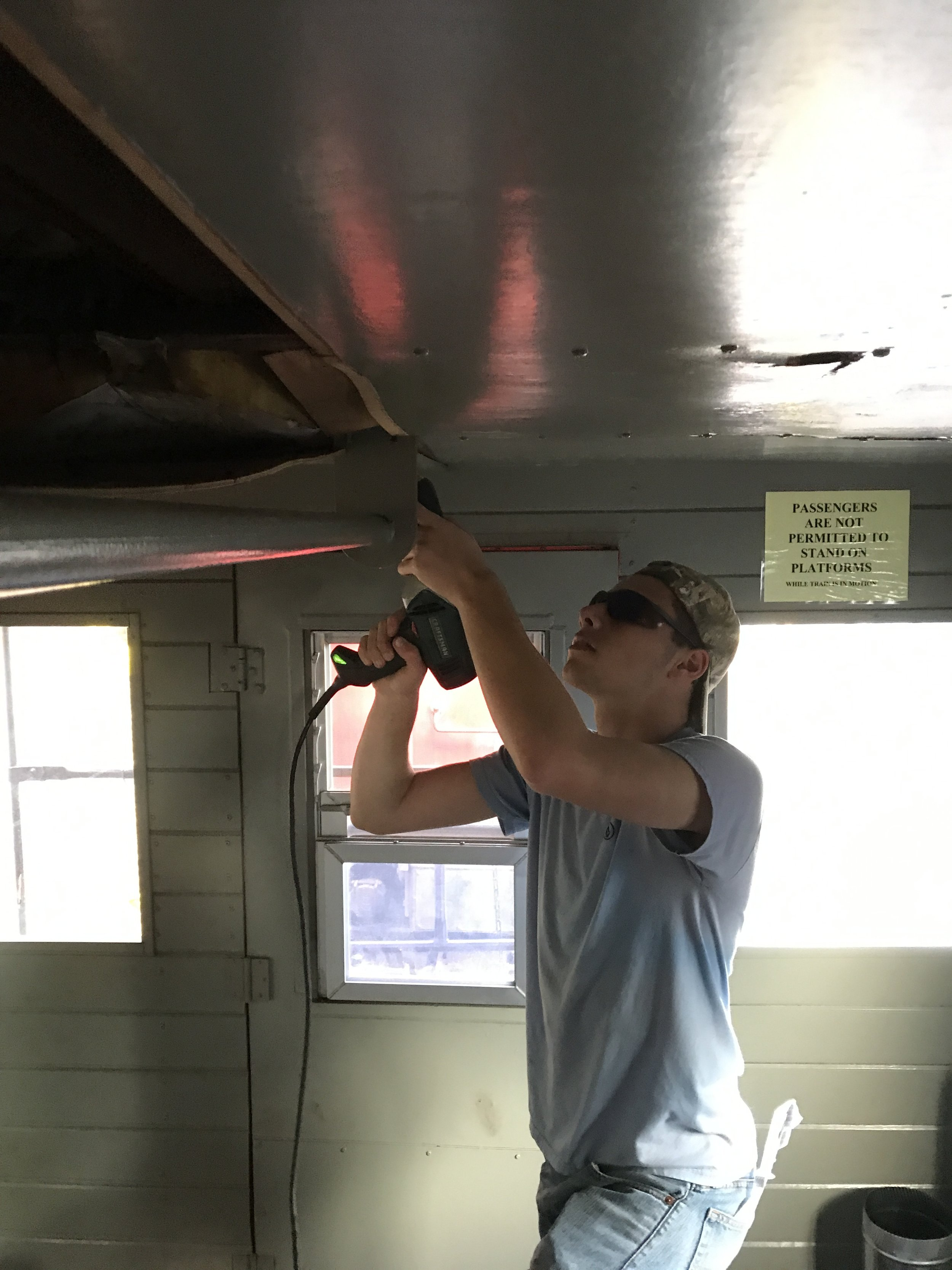 Matt Herman unscrewing wood panels which were used to replace the ceiling in part of the caboose which caught fire in the Conrail era.