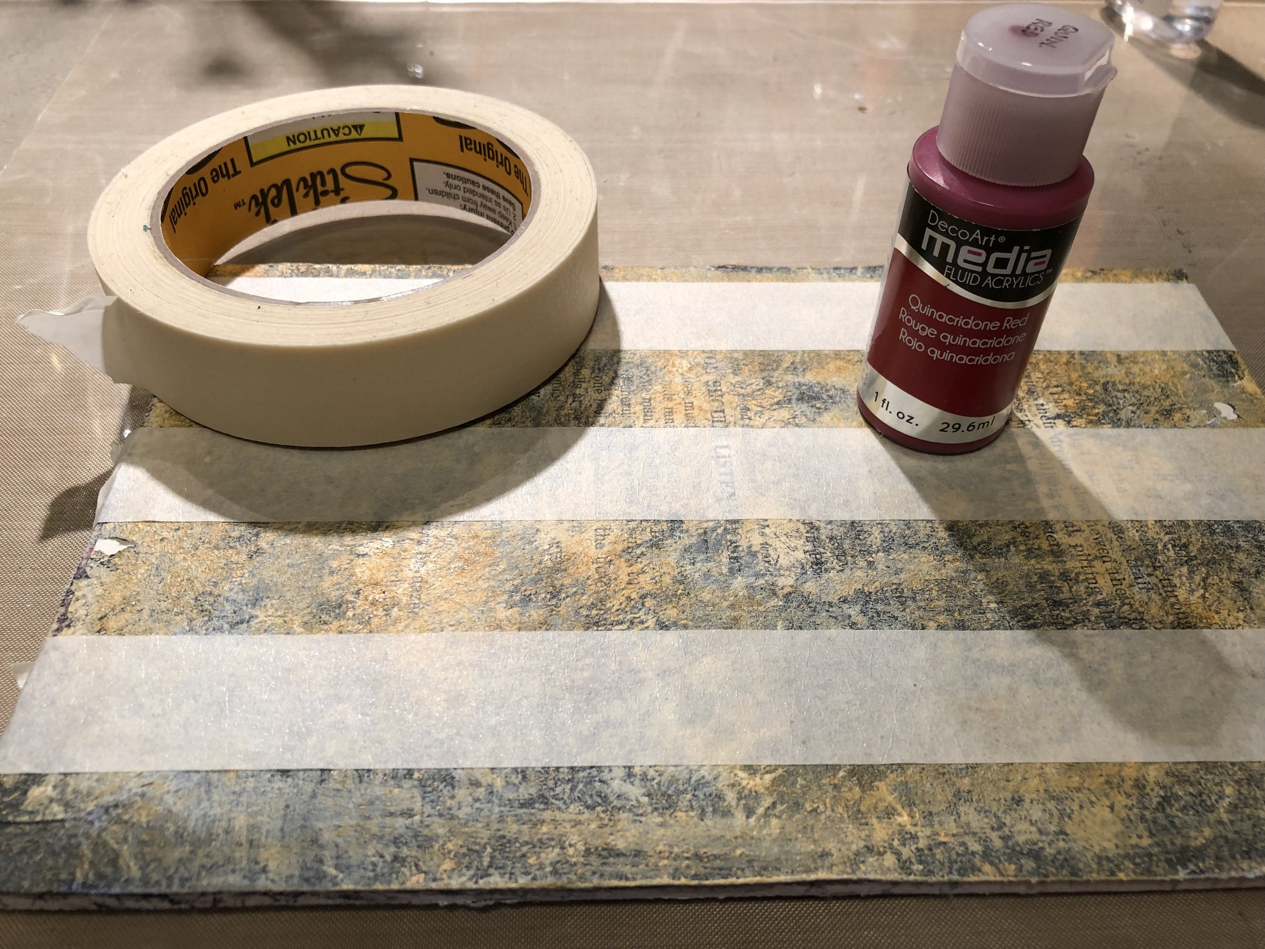 Using masking tape, block off some stripes. Then apply DecoArt Fluid Fluid Acrylic in Quinacridone Red.