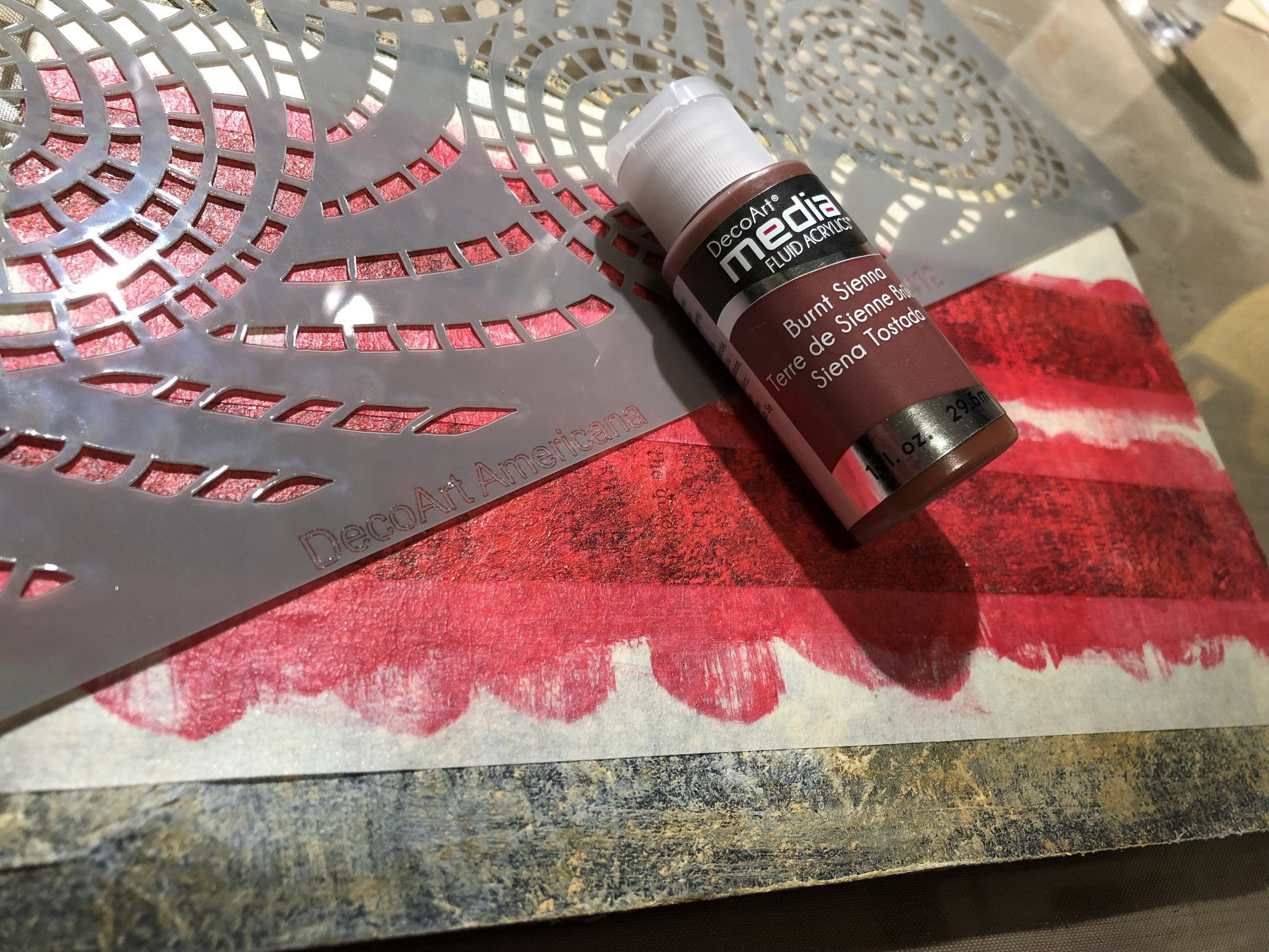 With a sponge and using DecoArt Americana's 'Segmented Swirls' stencil, apply DecoArt Media Fluid Acrylic in 'Burnt Sienna' over the red stripes.