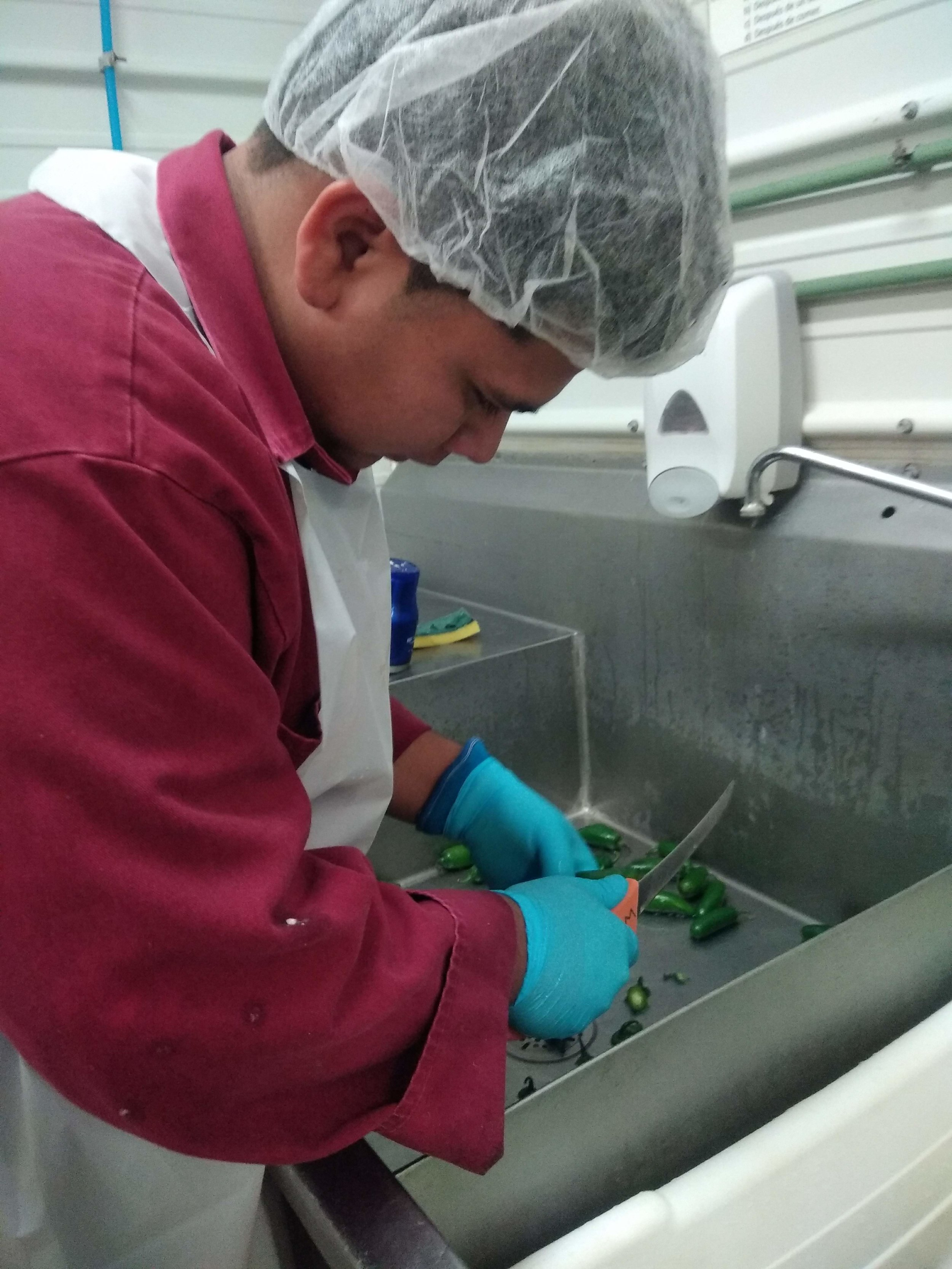 Miguel cuts the fresh jalepeños before adding them to the batch.