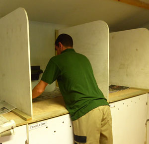 Volunteer Tom gets down to the nitty gritty -  papering night boxes in the mews room