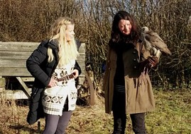Ellie watches on as Helen takes a Goshawk on the glove