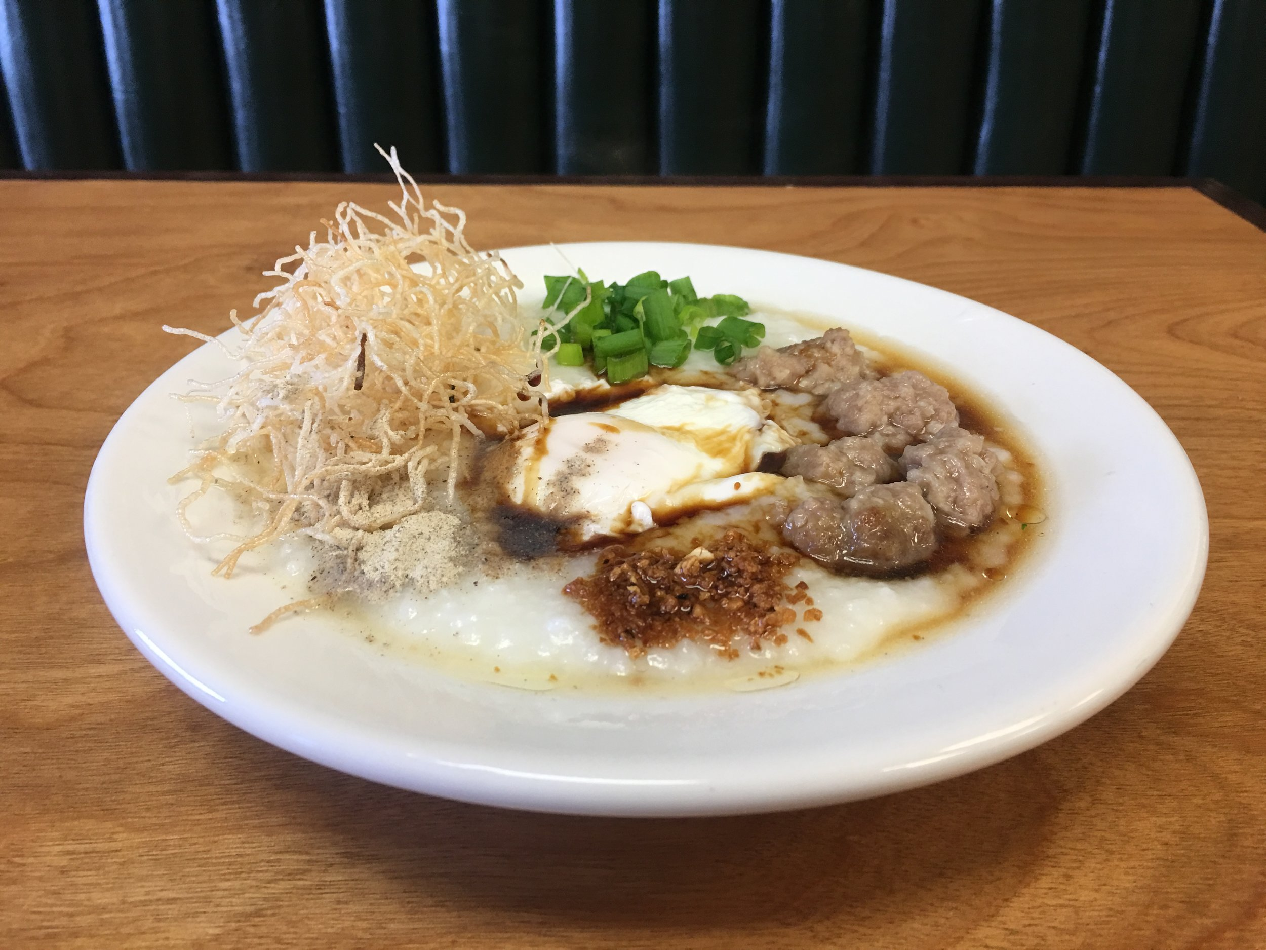Johk - Congee / rice porridge. Pictured here Bon Palay style with crispy rice noodles, scallion, a poached egg and moo deng (marinated ground pork and tapioca)