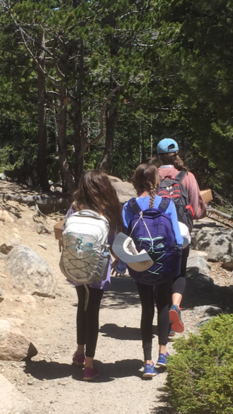 These two girls, after being baptized in a mountain lake, followed their leader, held hands and sang worship songs all the way back to the bus.