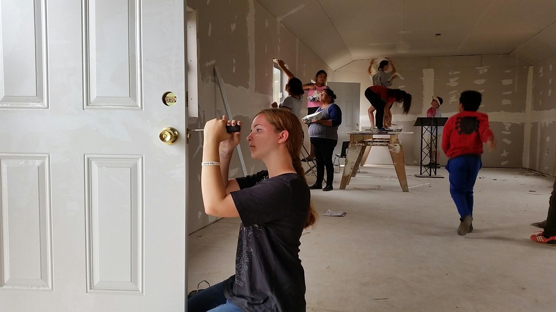 Katie installing a doorknob.