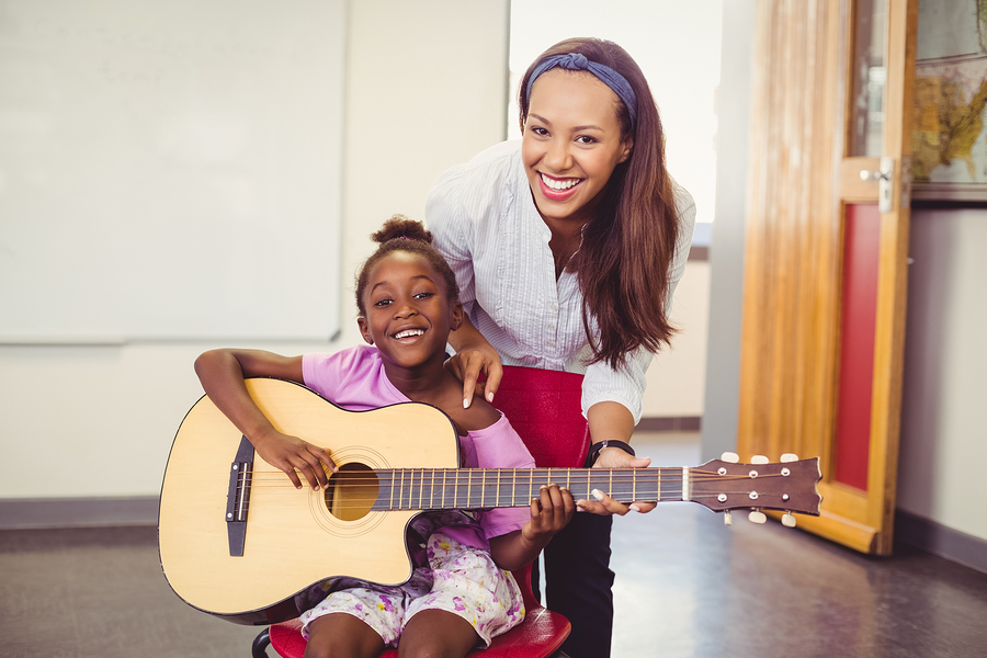 bigstock-Teacher-assisting-a-girl-to-pl-137251049.jpg