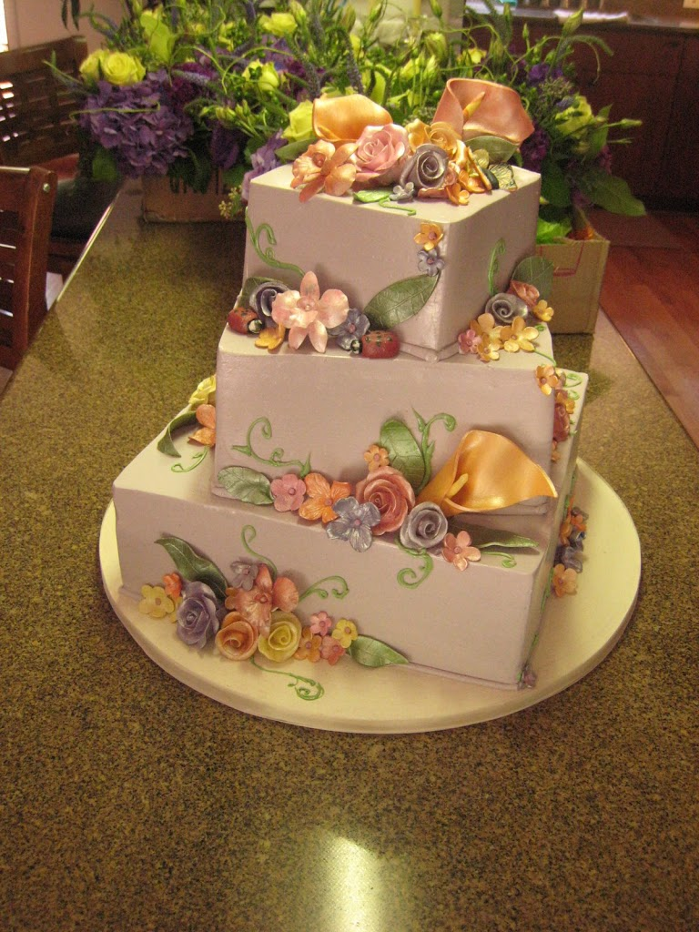 This fun wedding cake was iced in a lavender buttercream and covered with handmade sugar flowers