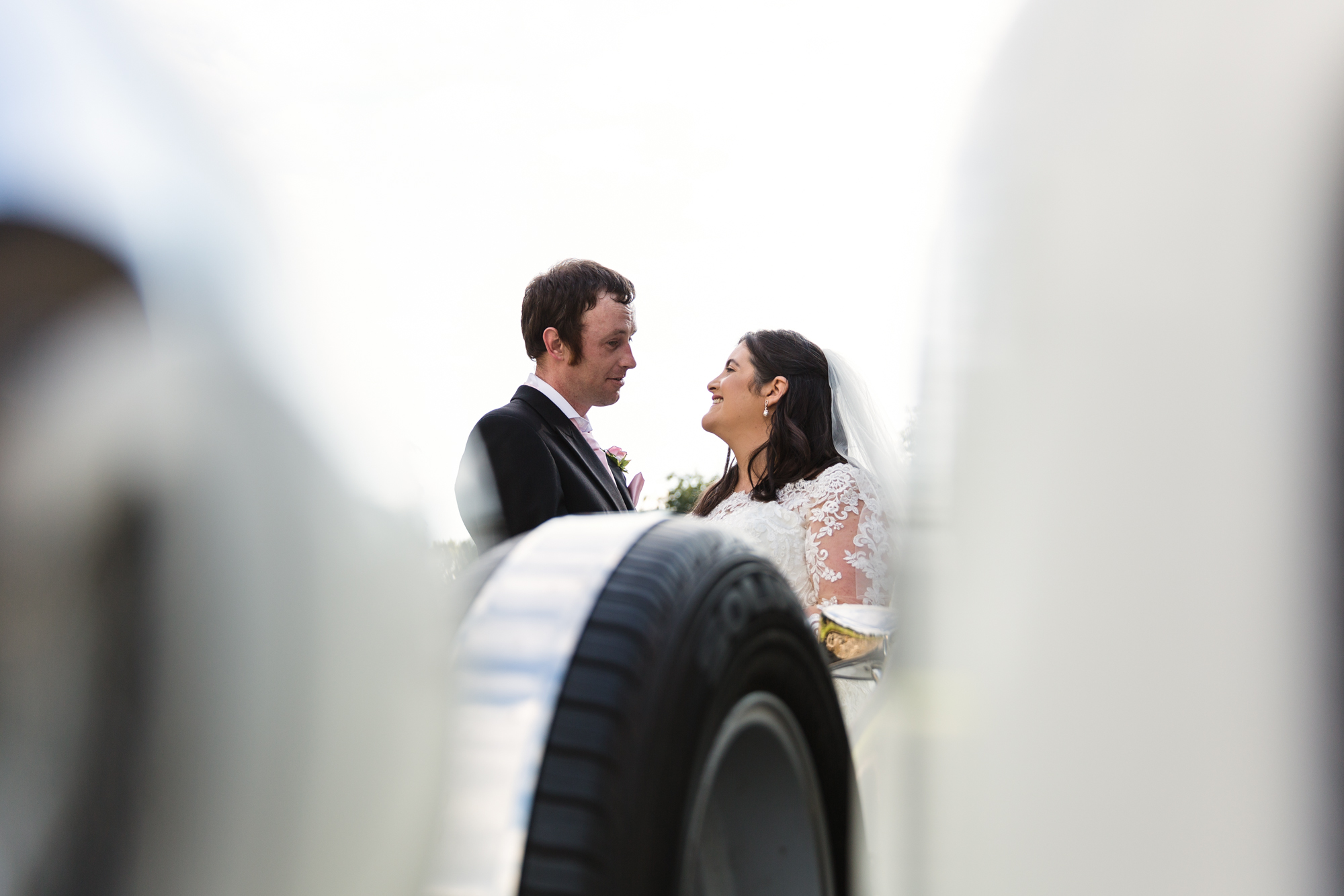 bride and groom portrait with wedding car at St Martins church Caerphilly