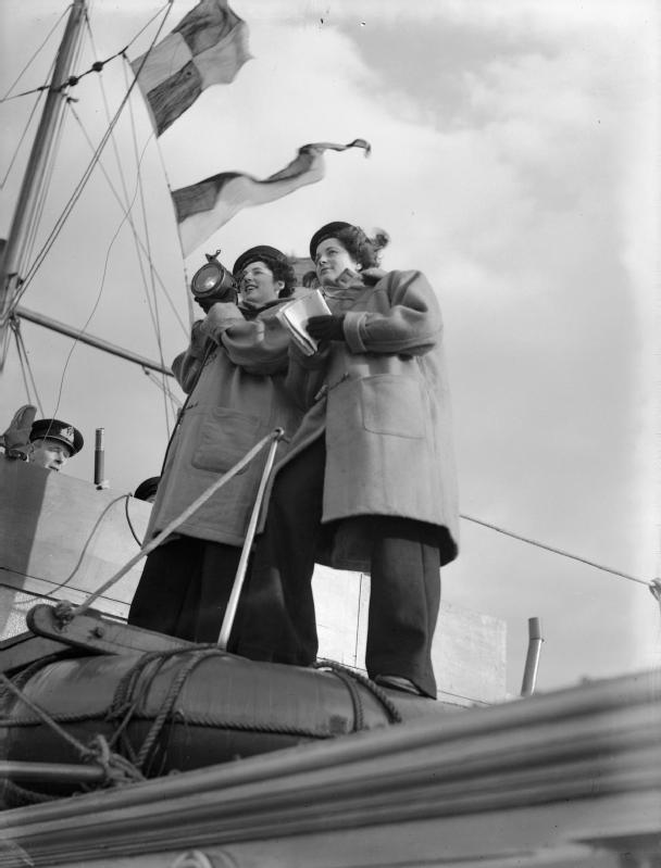 The Women's Royal Naval Service (wrens) gaining signalling experience on board a Royal Navy ship in Greenock, Scotland. Wearing an amazing pair of men's trousers.