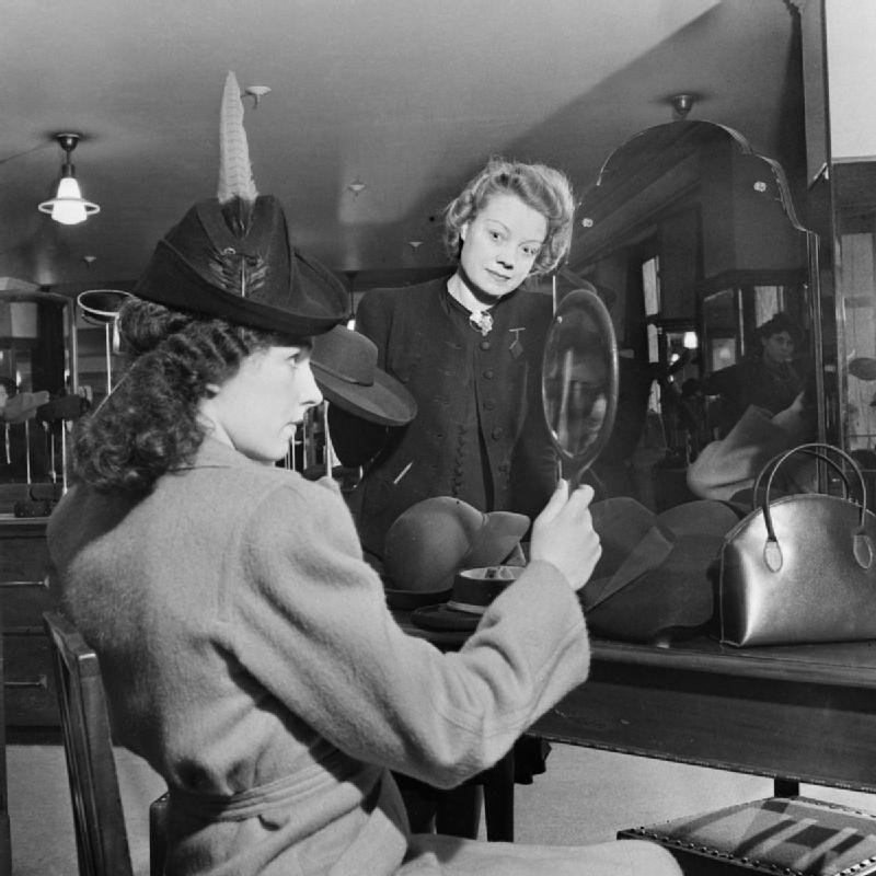 A customer tries on a new hat in the millinery department of Bourne and Hollingsworth on London's Oxford Street in 1942