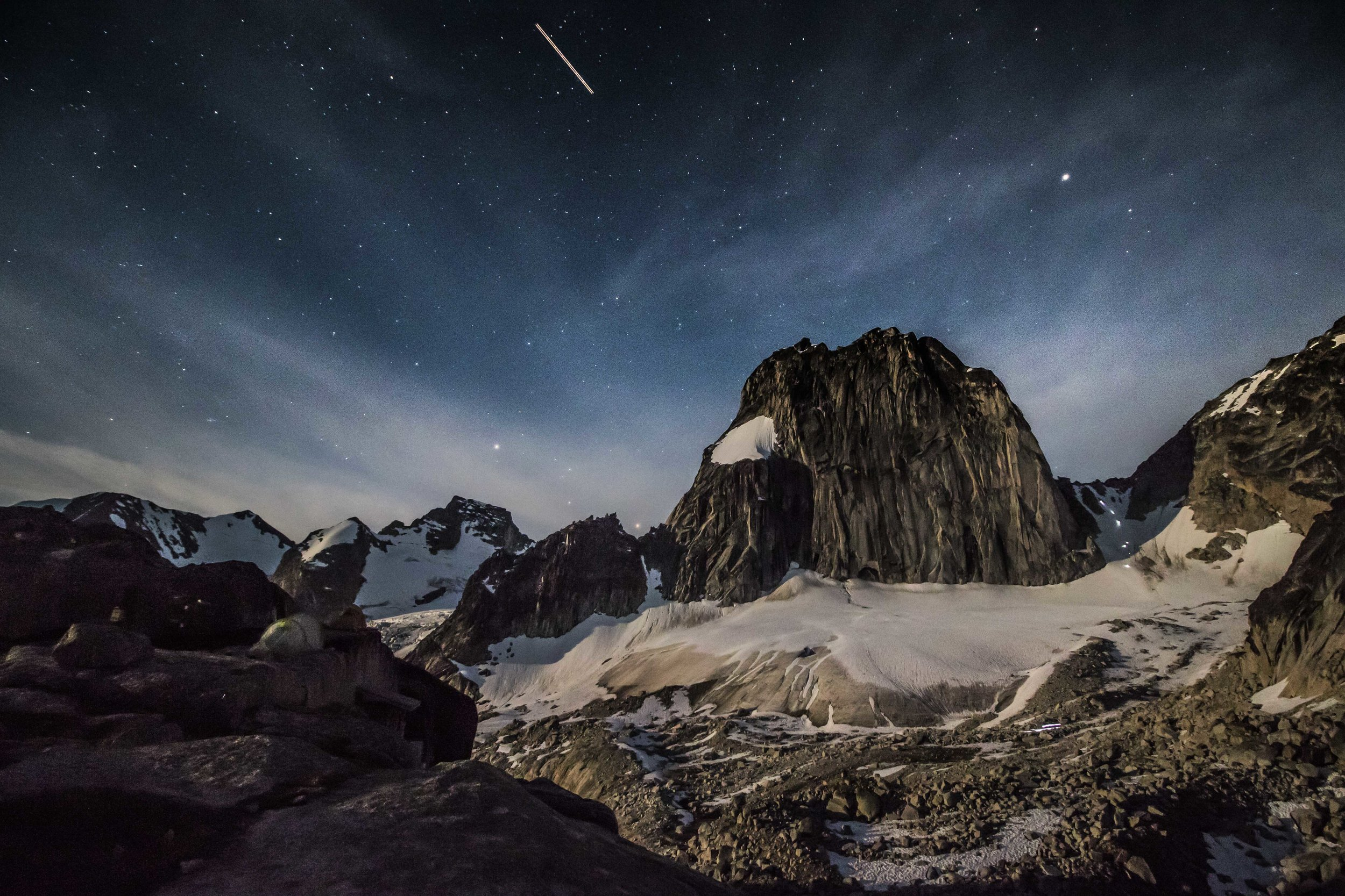 Looking at Snowpatch Spire from Applebee Camp, climbers descending the col by headlamp.